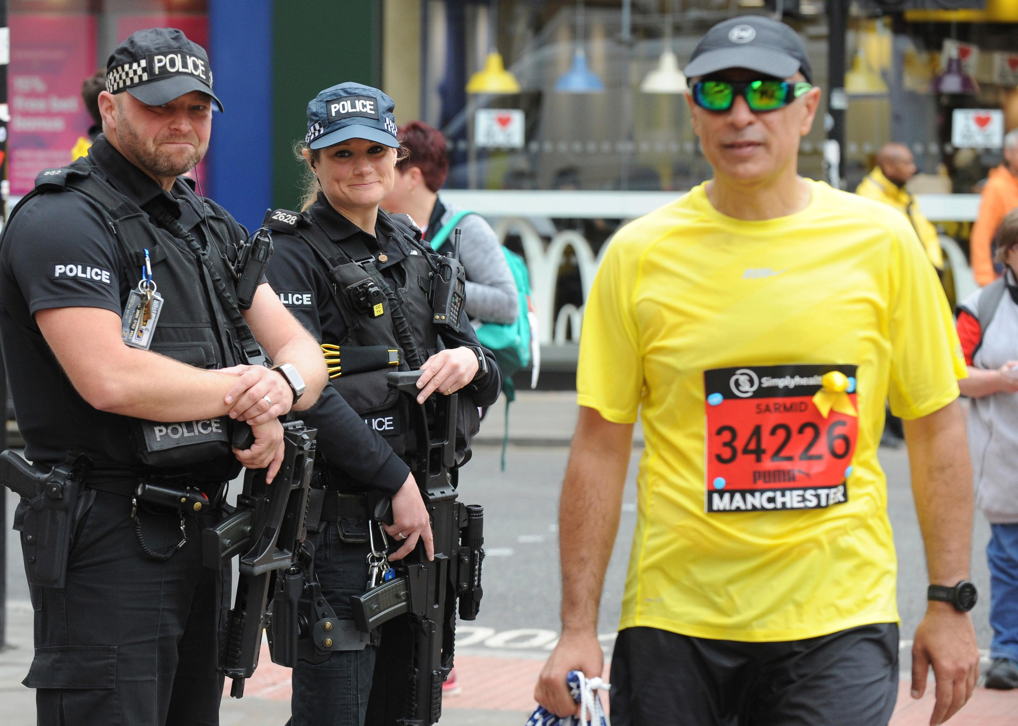 Armed response police guard the scene at the Great Manchester Run in central Manchester, England Sunday May 28 2017. More than 20 people were killed in an explosion following a Ariana Grande concert at the Manchester Arena late Monday evening. (AP Photo/Rui Vieira)