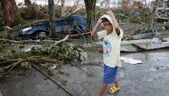 A boy walks past the devastation brought about by Haiyan at Tacloban. Roofs and windows were blown off and out of many of the buildings left standing.