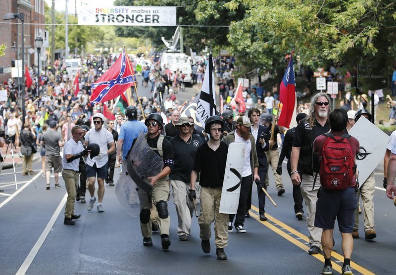 <p>FILE - In this Aug. 12, 2017 file photo, White nationalist demonstrators walk through town after their rally was declared illegal near Lee Park in Charlottesville, Va. A former federal prosecutor says the law enforcement response to a white nationalist rally this summer in Charlottesville that erupted in violence was a series of failures. The findings of former U.S. Attorney Tim Heaphy's monthslong investigation were unveiled Friday, Dec. 1. City officials asked him to conduct the review after facing scathing criticism over the Aug. 12 rally. (AP Photo/Steve Helber, File)</p>