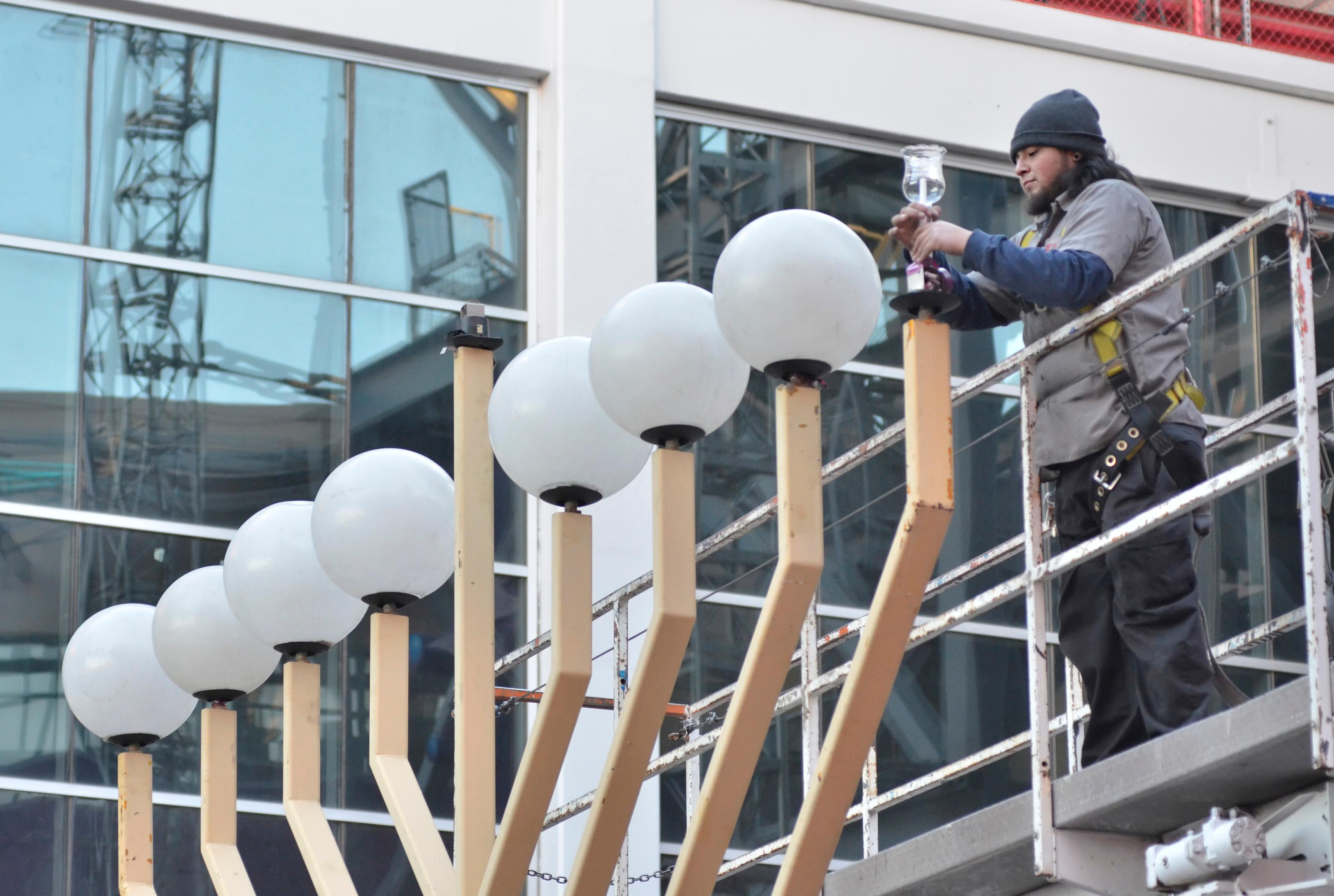 Brandon Escobar, a service technician with Yesco, mounts a candle onto a giant menorah before a lighting ceremony. Rabbi Shea Harlig, of the Chabad Jewish Center of Southern Nevada, Las Vegas Mayor Carolyn Goodman, Jonathan Jossel, CEO of the Plaza hotel-casino, and Patrick Hughes, President and CEO of Fremont Street Experience, were on hand for the first night of Hanukkah which was marked with the lighting of a 20-foot Grand Menorah on Fremont Street in downtown Las Vegas on Tuesday, Dec. 12, 2017. CREDIT: Bill Hughes/Las Vegas News Bureau