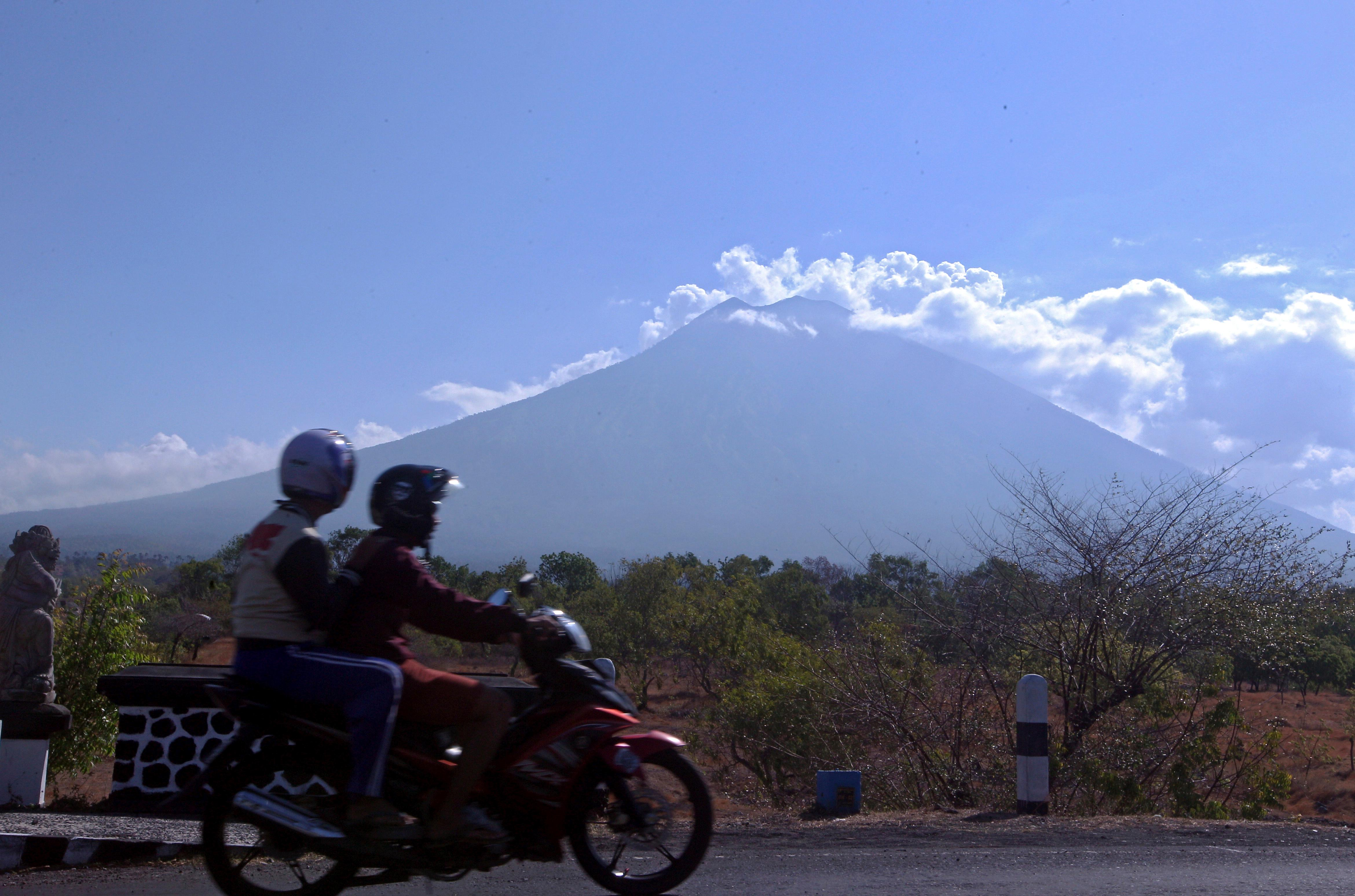 Motorists ride past by with Mount Agung volcano seen in the background in Karangasem, Bali, Indonesia, Thursday, Sept. 28, 2017. Warnings that the volcano on the tourist island will erupt have sparked an exodus as authorities have ordered the evacuation of villagers living within a high danger zone that in places extends 12 kilometers (7.5 miles) from its crater. (AP Photo/Firdia Lisnawati)