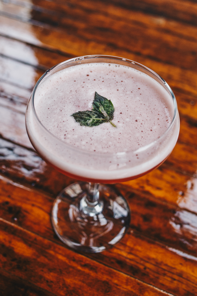 The Southern Belle: bourbon, Campari, pineapple juice, strawberry syrup, and peach bitters garnished with fresh mint{ }/ Image: Catherine Viox // Published: 3.24.19