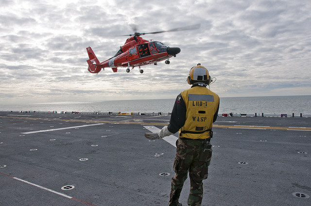 (Nov. 2, 2012) Aviation Boatswain's Mate (Handling) 3rd Class Andre Nation signals an MH-65D Dolphin helicopter assigned to Coast Guard Squadron 65 (CG 65) as it prepares to land on the flight deck of the amphibious assault ship USS Wasp. (U.S. Navy photo by Mass Communication Specialist Seaman Markus Castaneda/Released)