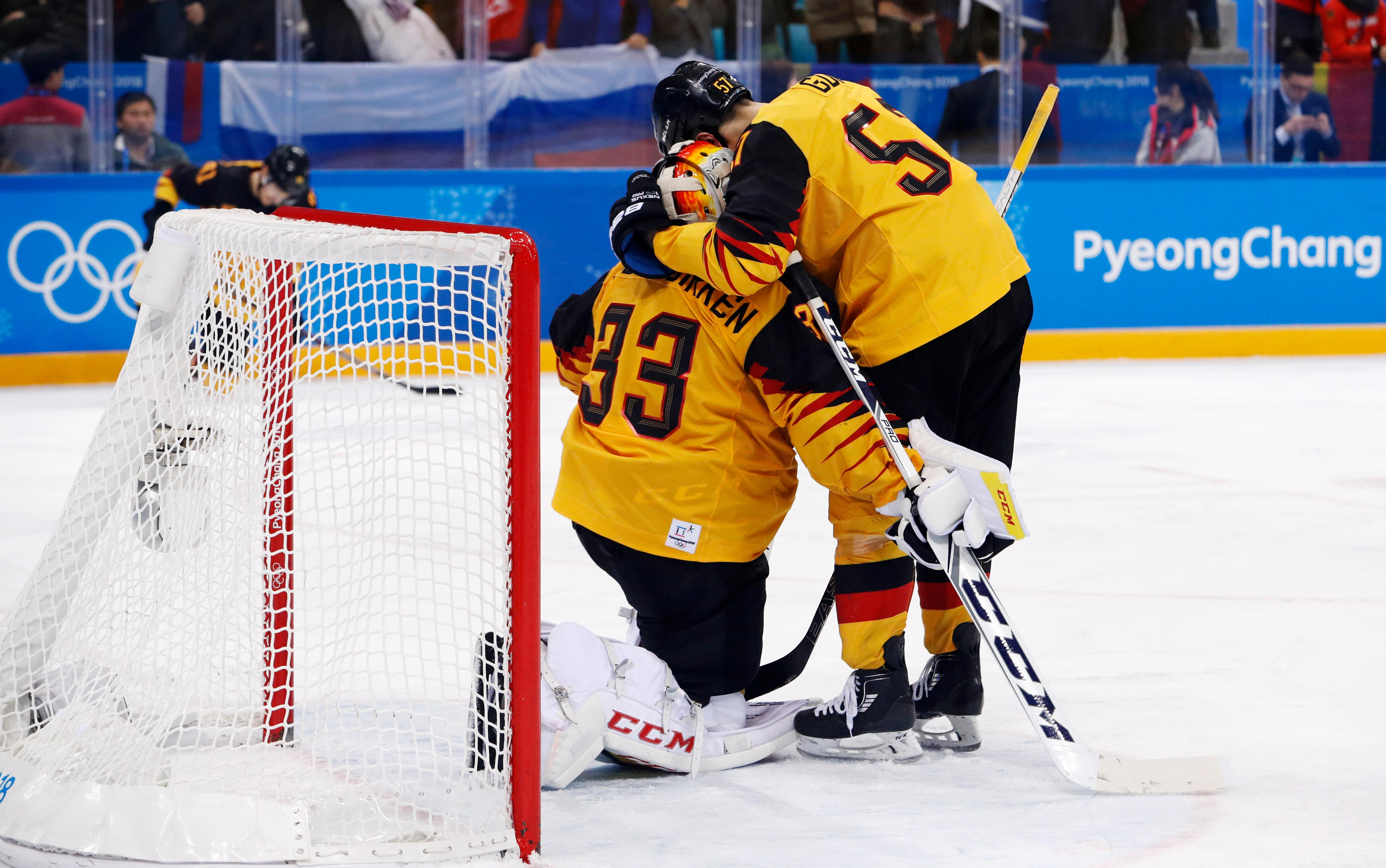 Marcel Goc (57), of Germany, and Danny aus den Birken (33) embrace after losing the men's gold medal hockey game against the Olympic athletes from Russia, 4-3, in overtime at the 2018 Winter Olympics, Sunday, Feb. 25, 2018, in Gangneung, South Korea. (AP Photo/John Locher)