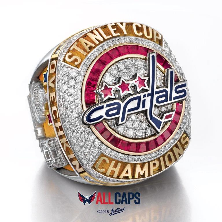 "The ring top features the Capitals logo – created from red and blue enamel – with the words ""STANLEY CUP CHAMPIONS"" set in yellow gold.{ }It's surrounded by 27 pavé-set diamonds that are encircled by 28 custom taper-cut rubies. The three star-shaped rubies set above the logo are inspired by the Washington, D.C. flag, where the stars represent D.C., Maryland and Virginia. (Image: Courtesy Washington Capitals)"