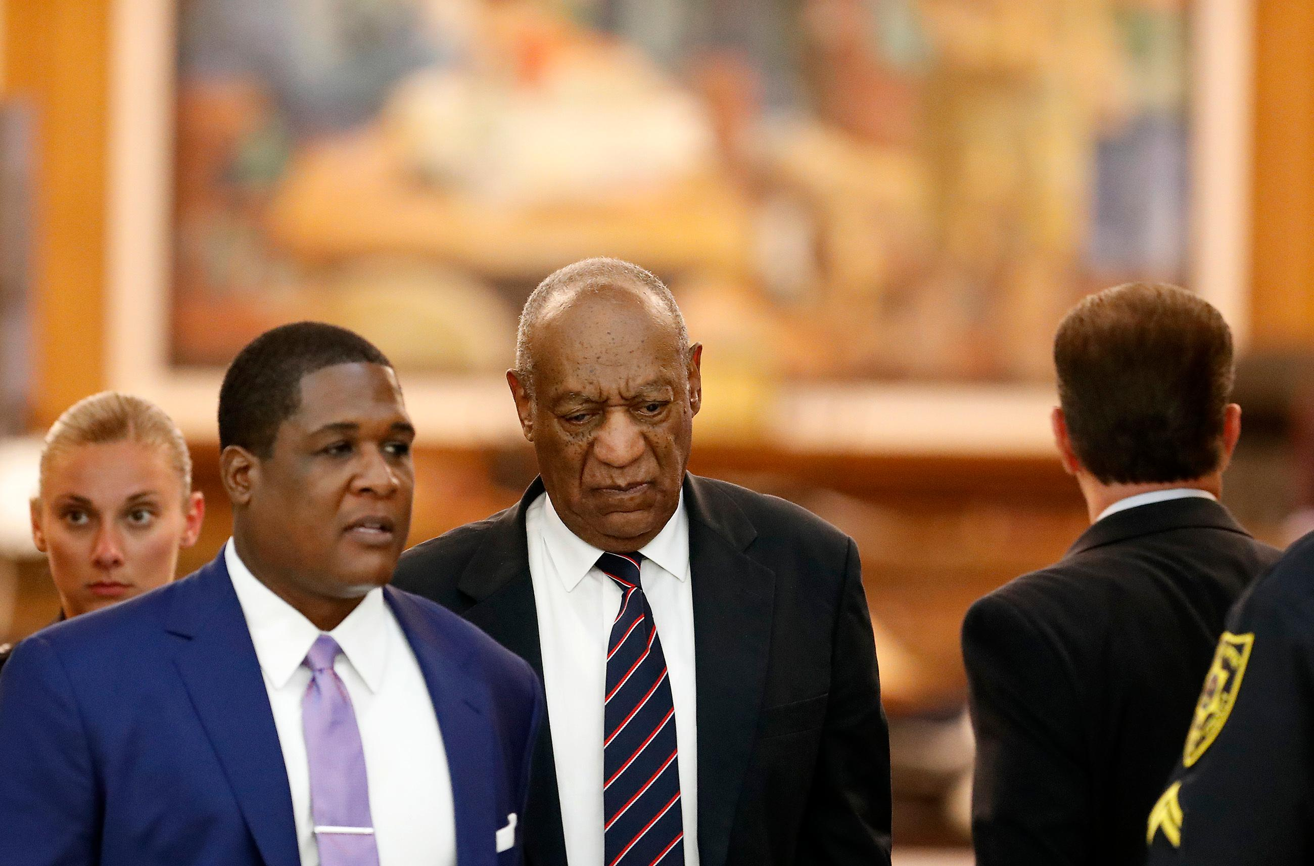 Andrew Wyatt, left, leads Bill Cosby, center, as they leave the Montgomery County Courthouse during Cosby's sexual assault trial in Norristown, Pa., Monday, June 12, 2017. (David Maialetti/The Philadelphia Inquirer via AP, Pool)