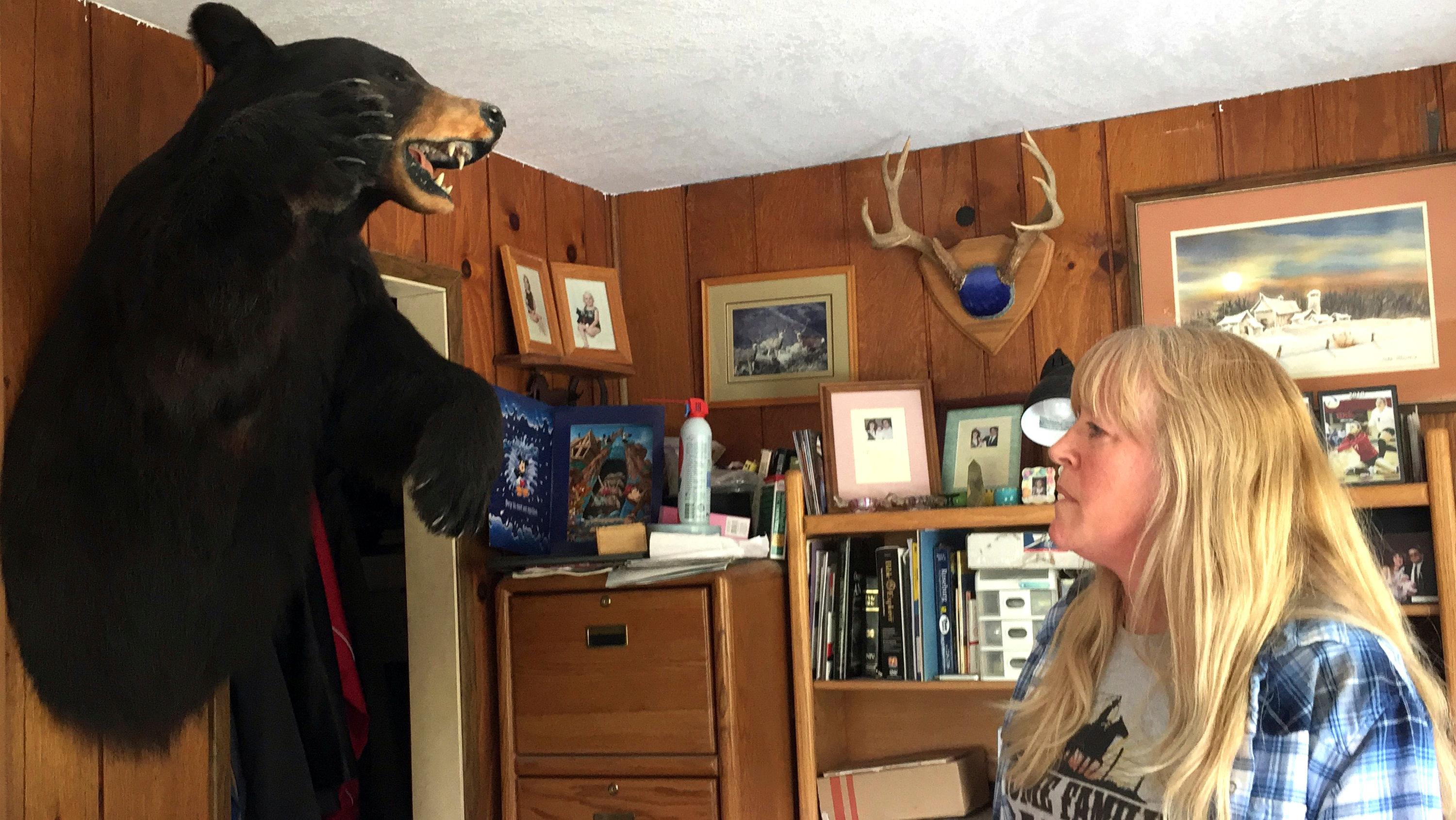 In this April 5, 2017 photo, longtime Tiller resident Paula Ellis shows off a bear head hanging on the wall in her home in Tiller, Ore. Ellis spent her childhood in Tiller hunting and riding horses and now worries about what will happen to the tiny, dying timber town. Tiller, a dot on a map in remote southwestern Oregon, is for sale for $3.5 million and the elementary school is for sale separately for $350,000.  (AP Photo/Gillian Flaccus)