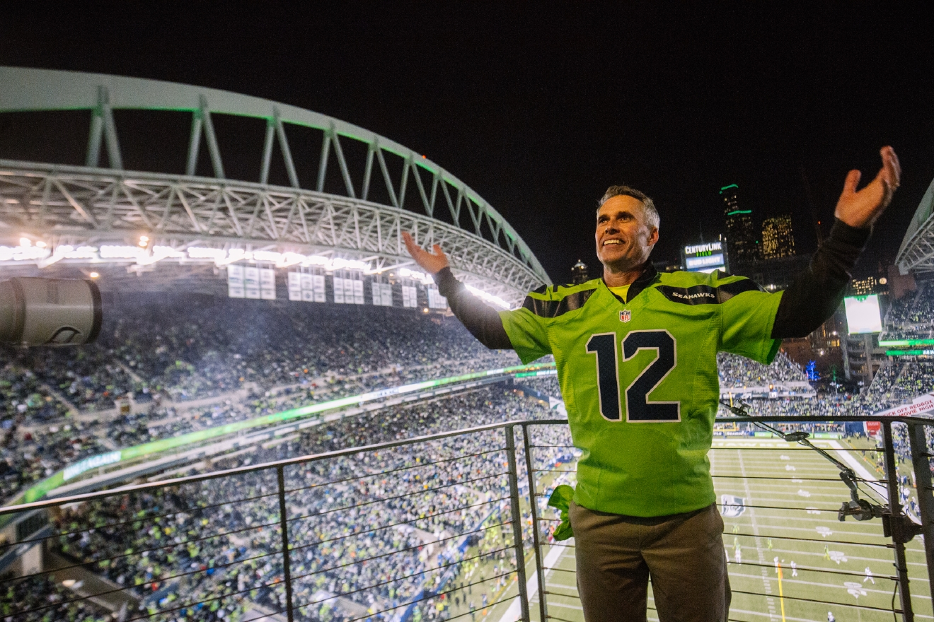 University of Washington Head Football Coach, Chris Petersen raised the 12th Man Flag at tonight's Seahawks game against the Rams. Coach Petersen has led the UW Huskies to the first ever College Football Playoff Berth that will be played on December 31st in Atlanta. December 15th, 2016. (Image: Joshua Lewis / Seattle Refined)
