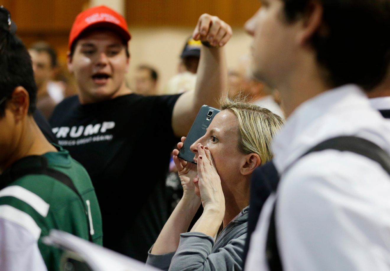 A protestor yells as she is pointed out to security personnel by an attendee at a rally for Republican presidential candidate Donald Trump in Eugene, Ore., Friday, May 6, 2016. The protestor made to leave the floor by security officials. (AP Photo/Ted S. Warren)