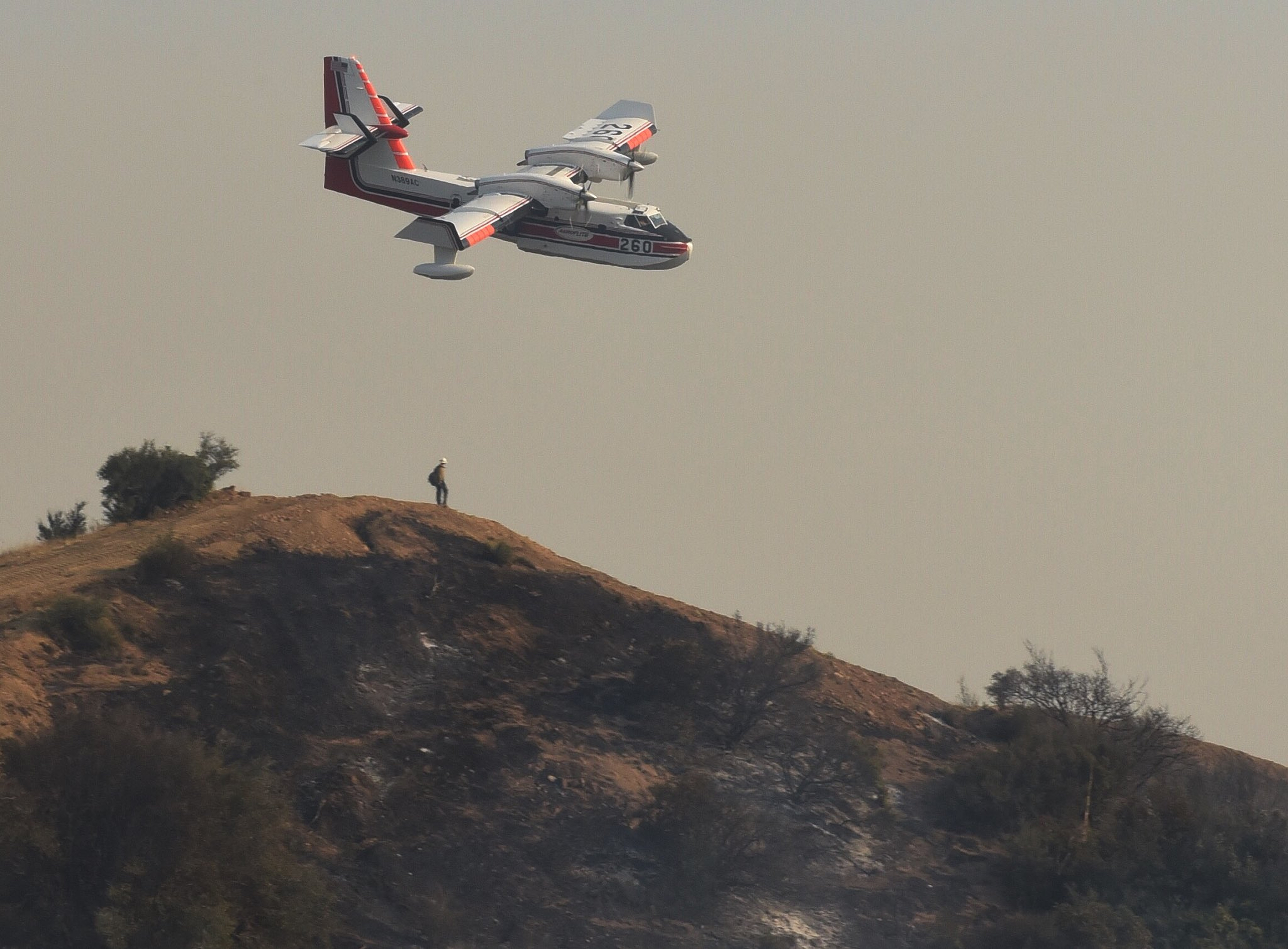 In this photo provided by the Santa Barbara County Fire Department, a Bombardier 415 Super Scooper aircraft comes in for a water drop below East Camino Cielo in the hills above Montecito, Calif., Sunday morning, Dec. 17, 2017. Thousands of firefighters tried Sunday to shield coastal communities from one of the biggest wildfires in California history while a funeral procession rolled past burn-scarred hillsides in honor of one of their colleagues who was killed battling the flames. (Mike Eliason/Santa Barbara County Fire Department via AP)