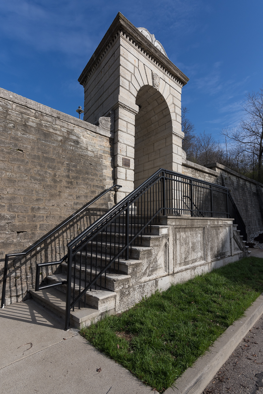 The arch and landing just beyond it were manufactured in the 1850s using limestone quarried from Dayton, Ohio. The Classical Revival stone arch (designed by French engineers) has an intentionally skewed alignment and serves as the riverfront's gateway to the Mt. Adams Steps. / Image: Phil Armstrong, Cincinnati Refined // Published: 4.13.18