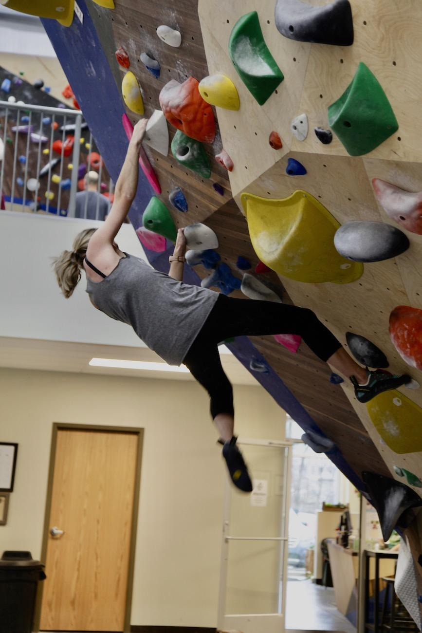 A boulderer looks to see where to place her feet next to allow her to move up the bouldering 'problem' or puzzle-like route to navigate. Problems are rated by difficulty level. / Image: Chez Chesak // Published: 2.1.20