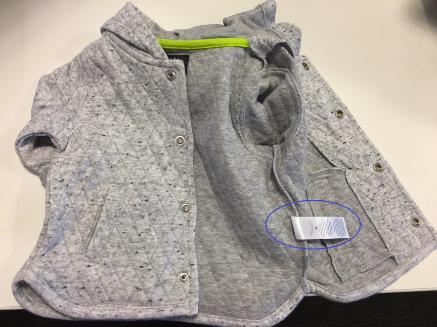 The style number can be found on the front of the care tag sewn on the inside of the jacket. The UPC number can be found on the back of that tag. (Photo: U.S. Consumer Product Safety Commission)<p></p>
