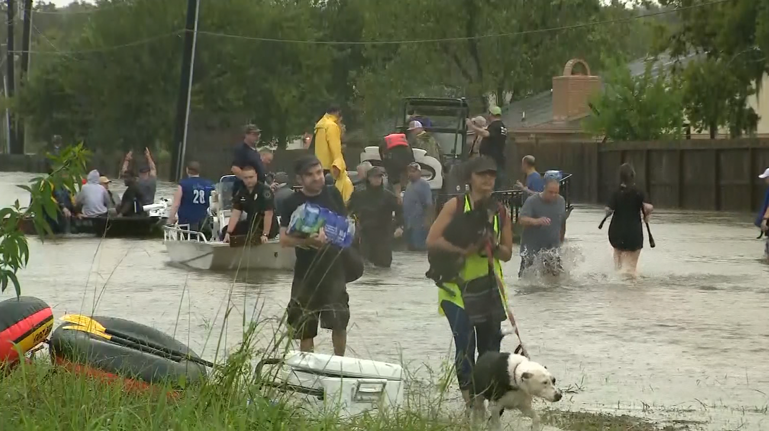 People with boats on flooded street (KPRC/CNN)