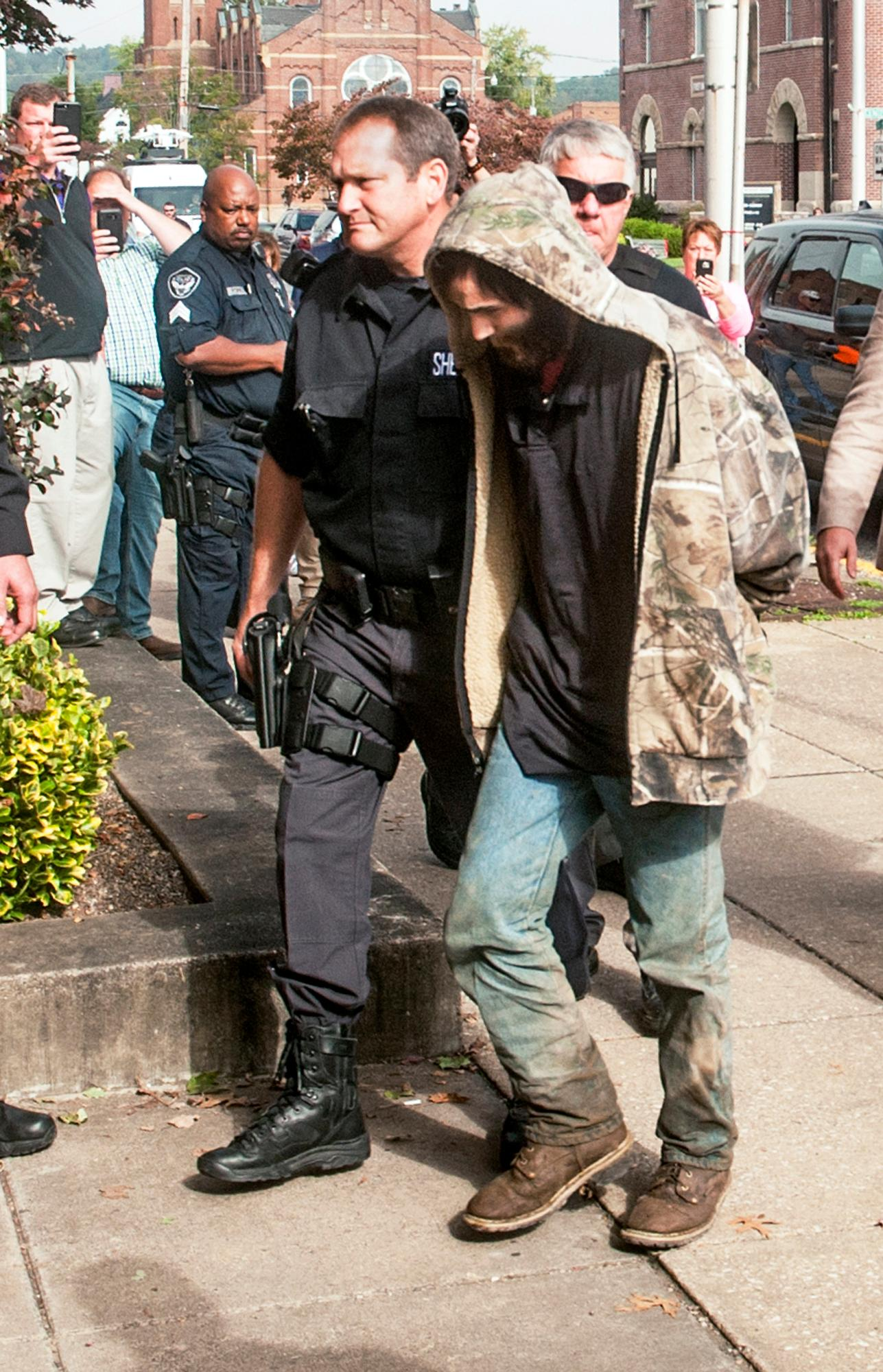Suspect Arron Lawson, 23, is escorted into the Lawrence County Courthouse, Friday, Oct. 13, 2017 by Sheriff Jeff Lawless, left, of the Lawrence County Sheriff's Office in Ironton, Ohio. He was arrested roughly 12 miles (19 kilometers) south of where authorities found three adults dead in a house trailer on Wednesday evening.(Jessica St. James/Ironton Tribune via AP)