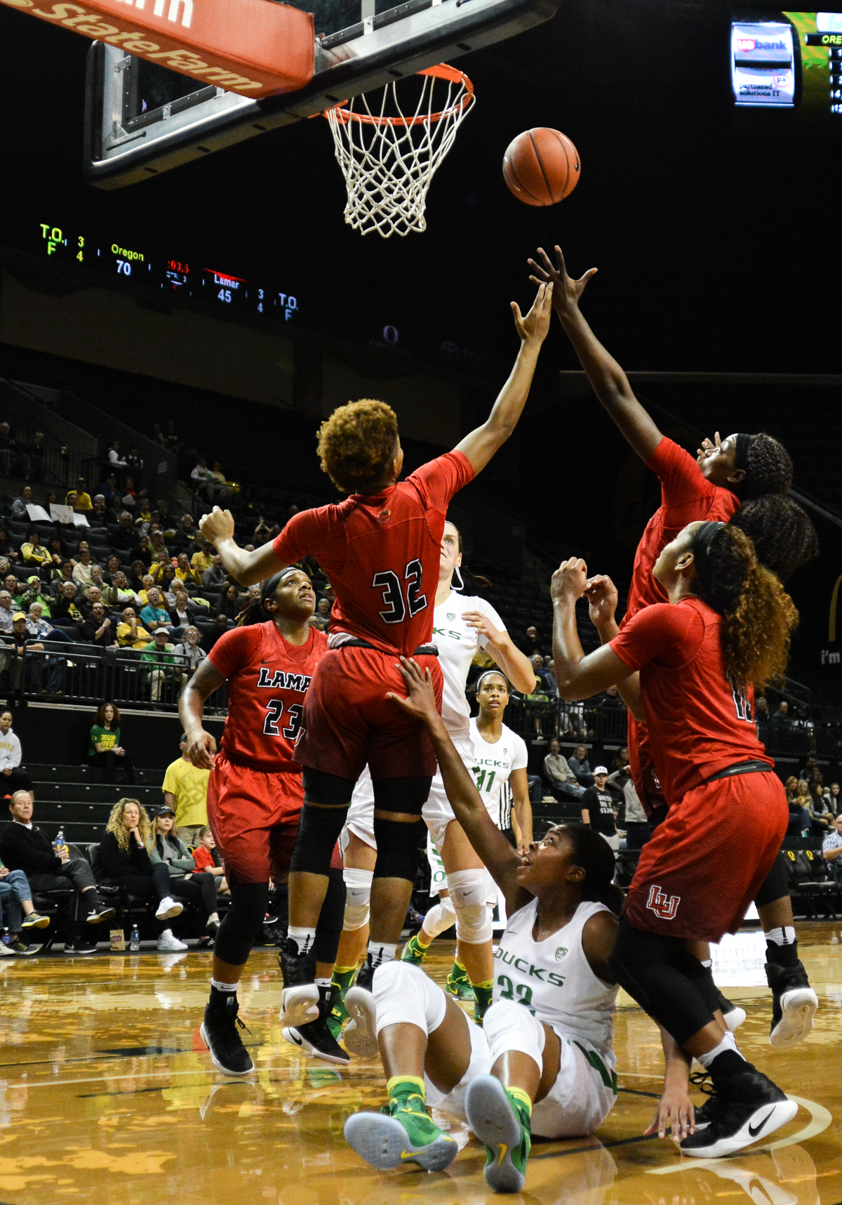 Ducks Oti Gildon (#32) gets knocked down while two Cardinal defenders fight for the ball over her. The Oregon Ducks women's basketball team won their season opener against the Lamar Cardinals 84-67. Photo by Jacob Smith, Oregon News Lab