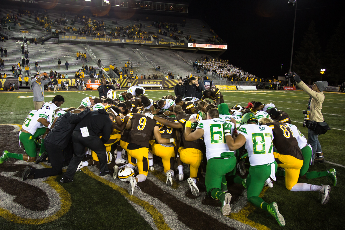 Players from the Cowboys and Ducks joined together at centerfield for a postgame prayer. The Oregon Ducks recorded their first road win under head coach Willie Taggart with their 49-13 victory over the Wyoming Cowboys on a cold night at War Memorial Stadium in Laramie, Wyoming.  Photo by Austin Hicks, Oregon News Lab