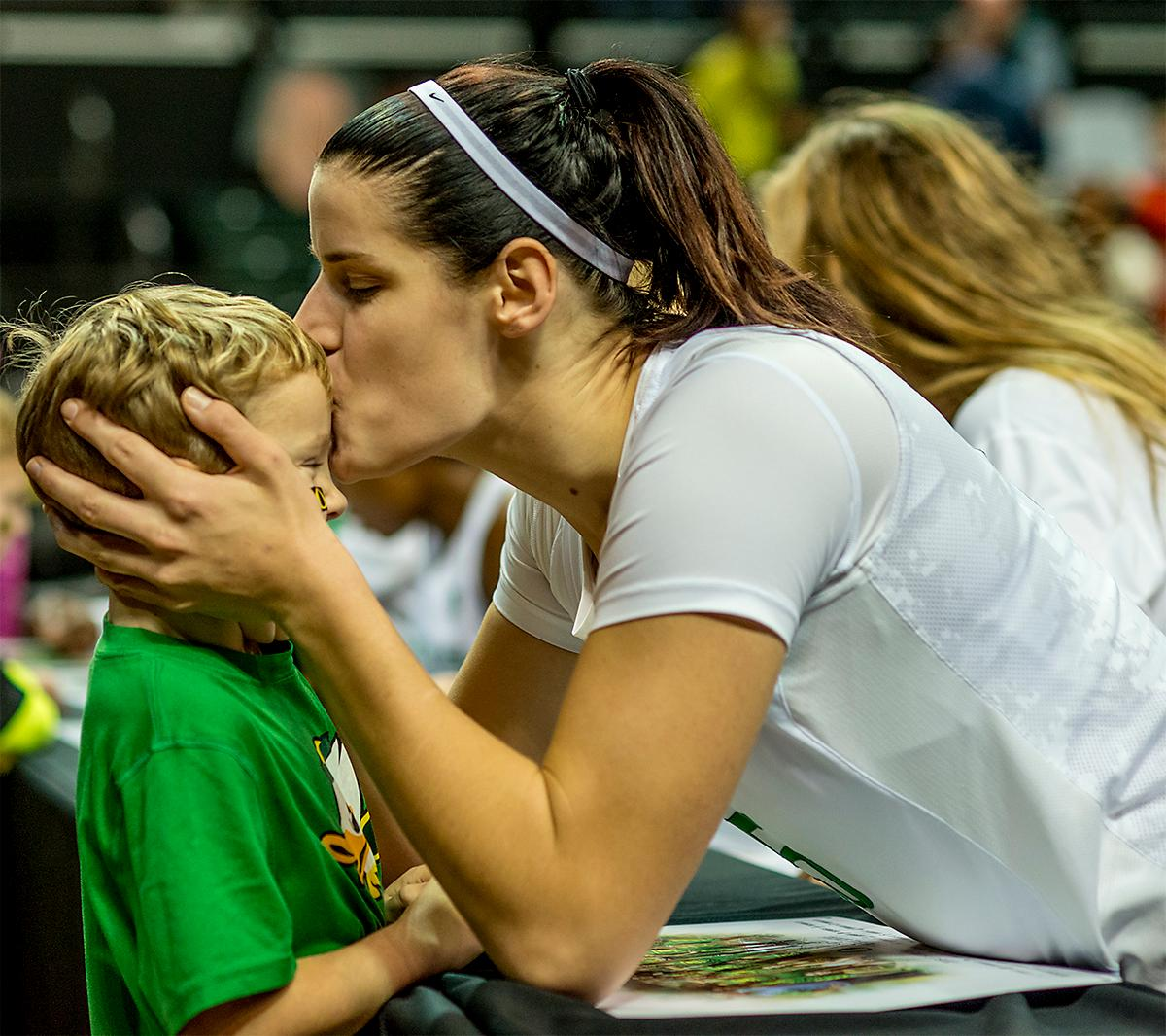 The Duck's Jacinta Vandenberg (#15) gives a young fan a kiss as the Ducks team signs autographs after the game. The UO Ducks Women's basketball team took the win against Idaho on Tuesday at Matthew Knight Arena, 73-70, in a game that saw the Ducks force a miss at the buzzer. Maite Cazorla (#5) achieved a double-double with 14 points and 10 assists. Lexi Bando (#10) added 17 points, and made 5 out of 6 three pointers. The Ducks are now 10-2 this season. Photos by August Frank, Oregon News Lab