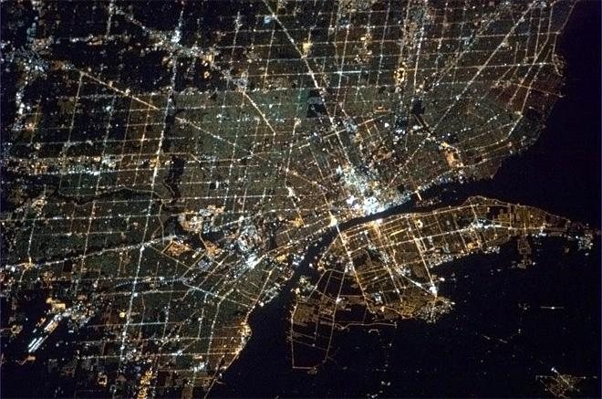 80 - Detroit and Windsor, where Michigan meets Ontario. Spiderwebs of light expanding out from the dark river border. (Photo & Caption: Chris Hadfield/NASA)