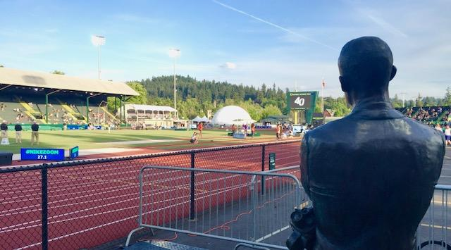 The Famous statue of Bill Bowerman standing at the stretch of Hayward Field known as 'Bowerman's Curve.' Photograph courtesy of Zachary Neel.{ }