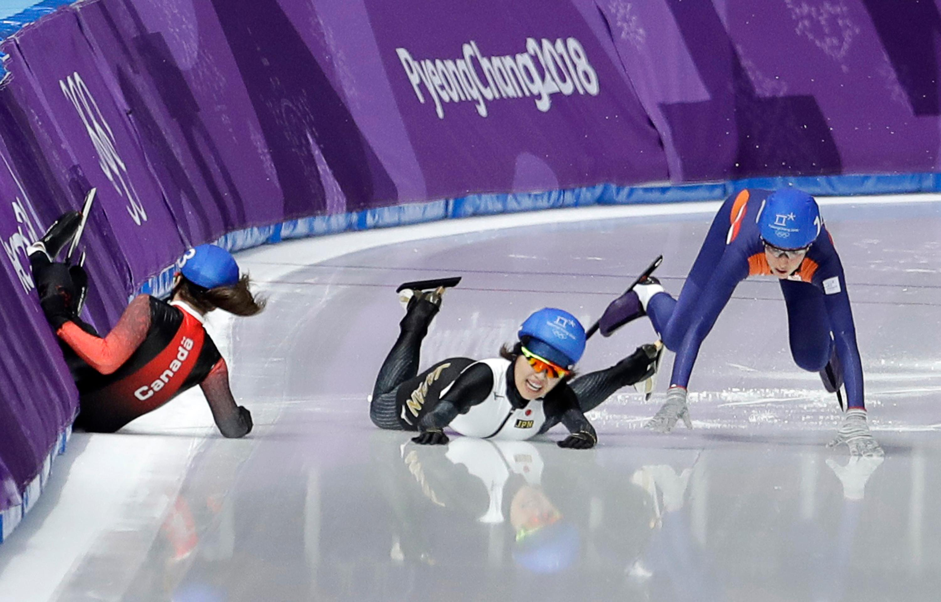 Ivanie Blondin of Canada, Ayano Sato of Japan, and Annouk van der Weijden of The Netherlands, from left to right, crash during the women's mass start speedskating race at the Gangneung Oval at the 2018 Winter Olympics in Gangneung, South Korea, Saturday, Feb. 24, 2018. (AP Photo/Petr David Josek)
