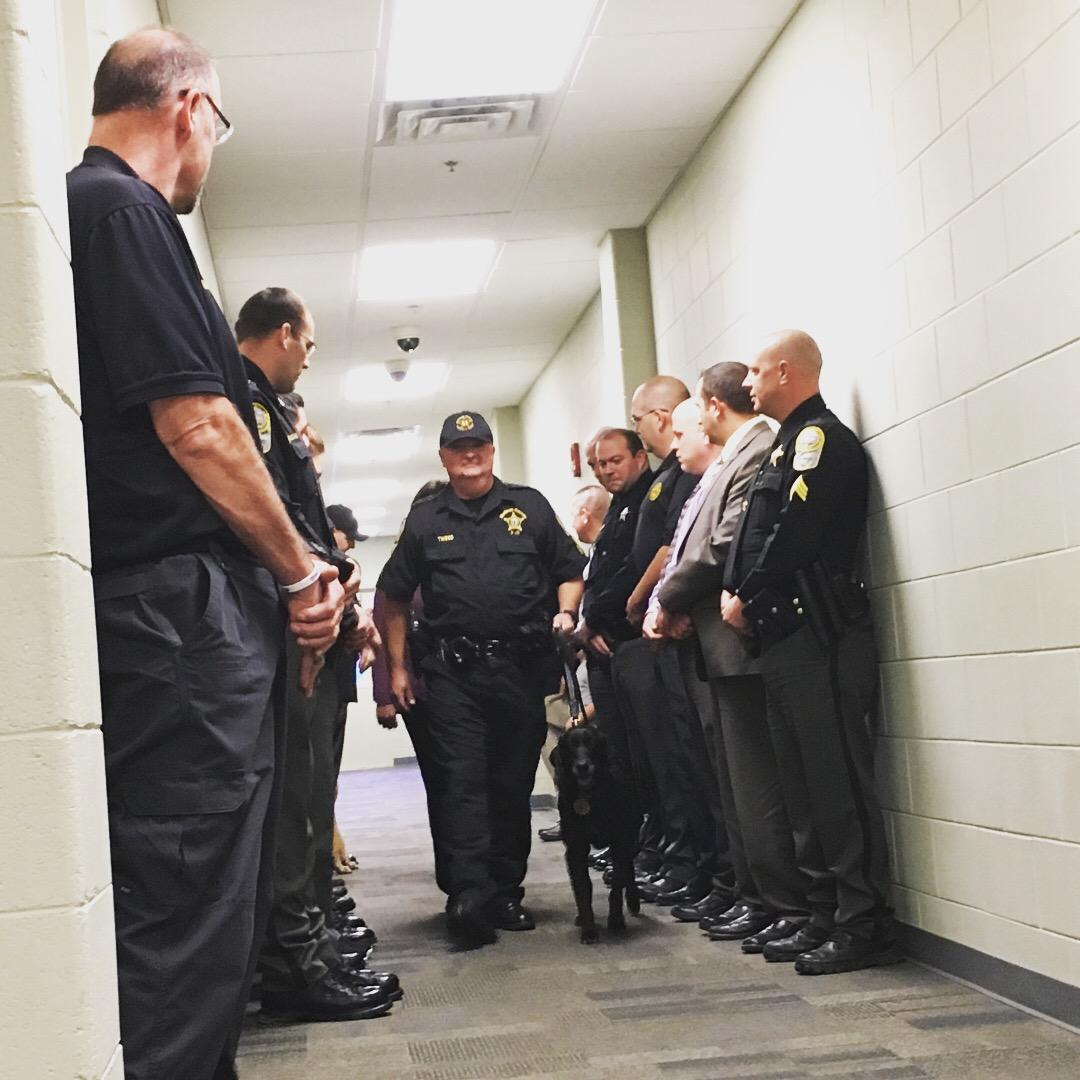 Emotions ran high at a retirement ceremony for a K-9 diagnosed with cancer. Sheriff Buddy Harwood and deputies stood in the hallway as Sgt. Jeff Tweed walked his four-legged partner Tyler to the event. (Photo credit: WLOS staff)