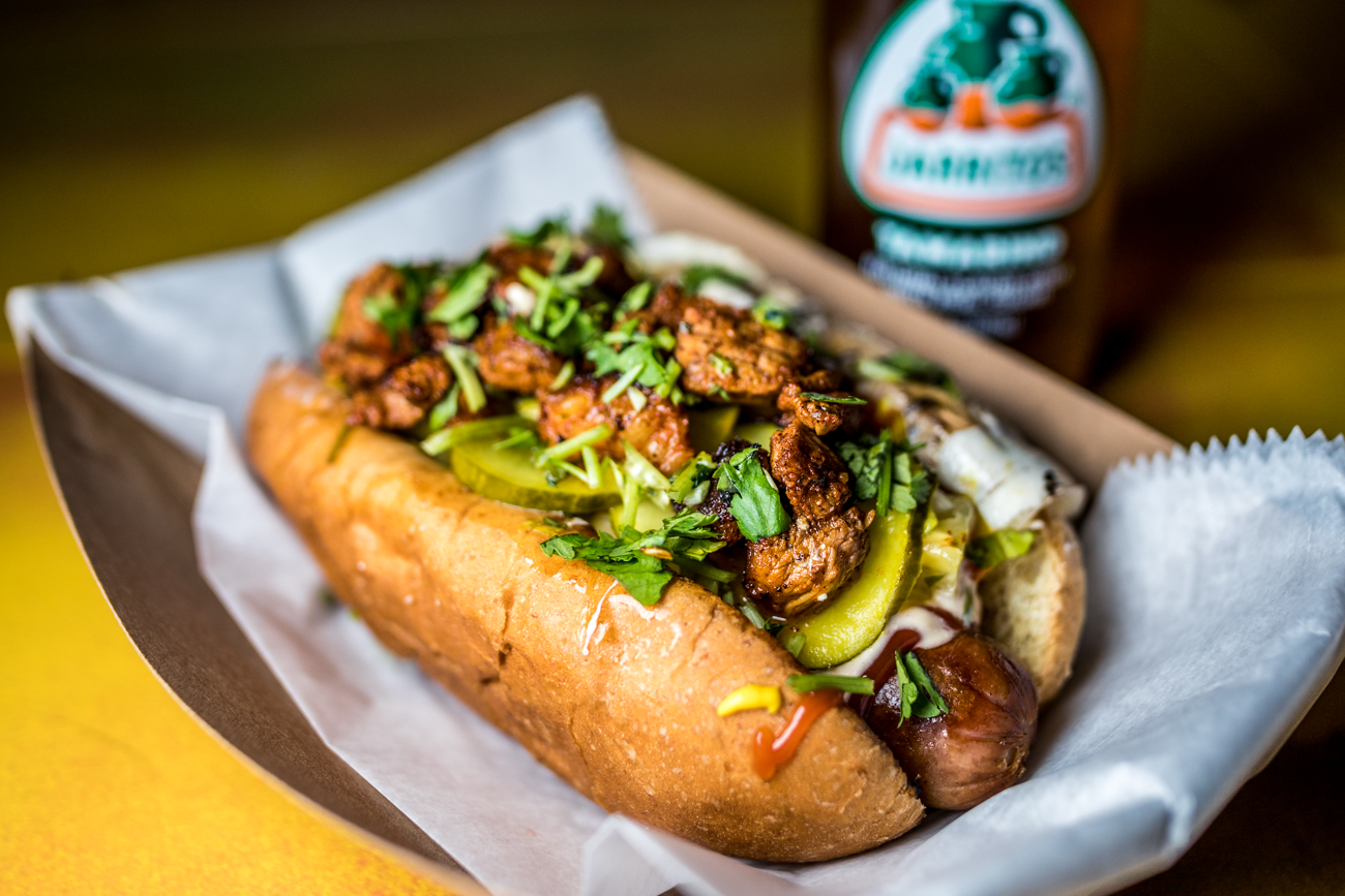 Al Pastor Papi Jochos: Papi's all-beef hot dog, grilled onions, grilled pastor pork, queso oaxaca, pineapple salsa, ketchup, mustard, mayo, tomato, house pickles, cotija, and cilnatro / Image: Catherine Viox{ }// Published: 8.24.20