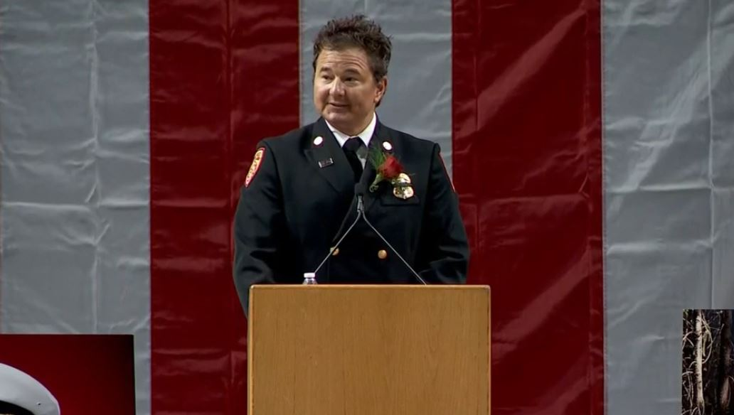 <p>Dominic Burchett stepped up to the podium and go into a caricature of Matthew Burchett by messing up his hair before telling the audience to stand, clap and cheer in the fallen Battalion Chief's honor. (Photo: KUTV)</p>