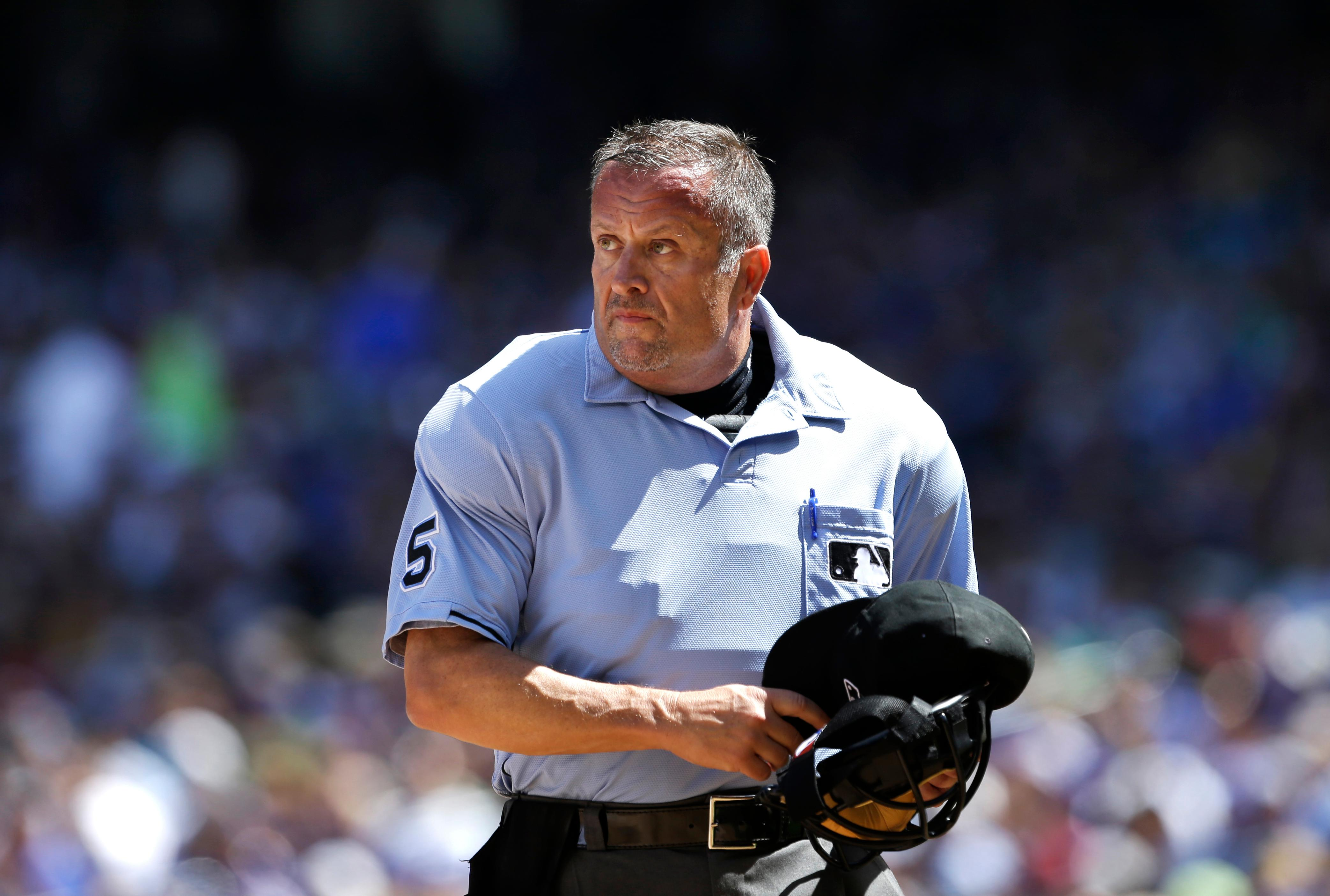 FILE - In this Aug. 7, 2013, file photo, Major League Baseball umpire Dale Scott prepares to return to action after being injured in the second inning of a baseball game between the Mariners and Toronto Blue Jays in Seattle. Rather than risk yet another concussion, Scott has decided to retire at 58. The veteran crew chief missed nearly the entire 2017 season after a foul ball off the bat of Baltimore slugger Mark Trumbo in Toronto on April 14 caught him hard in the mask, causing Scott's second concussion in nine months and fourth in five years. (AP Photo/Elaine Thompson, File)