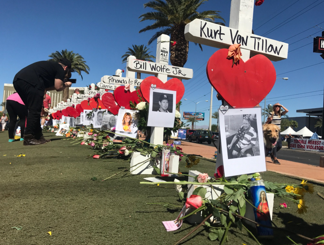 Flowers, candles, balloons, and memorial crosses cover the turf under the iconic Welcome to Las Vegas sign. (Kelsey Thomas | KSNV)