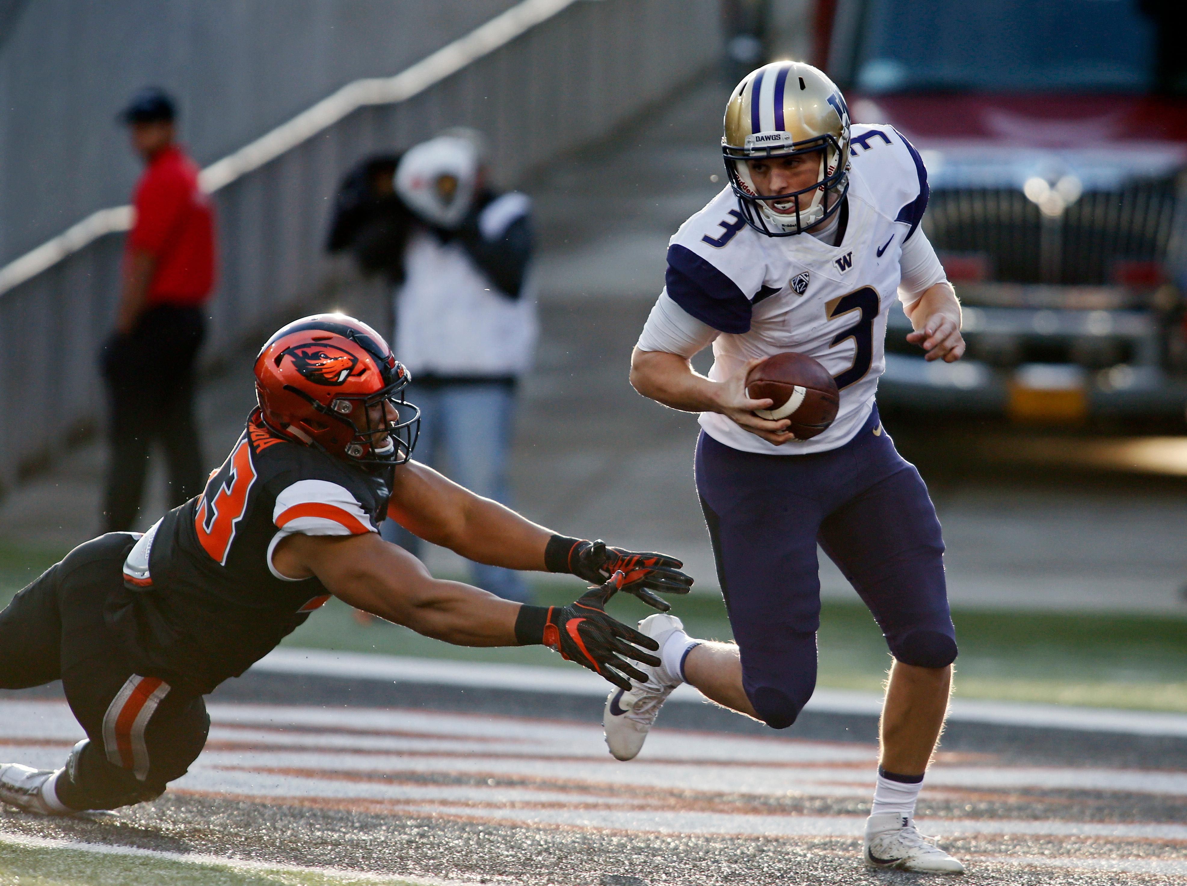 Washington quarterback Jake Browning (3) escapes the tackle attempt by Oregon State's Titus Failauga in the first half of an NCAA college football game, in Corvallis, Ore., Saturday, Sept. 30, 2017. (AP Photo/Timothy J. Gonzalez)