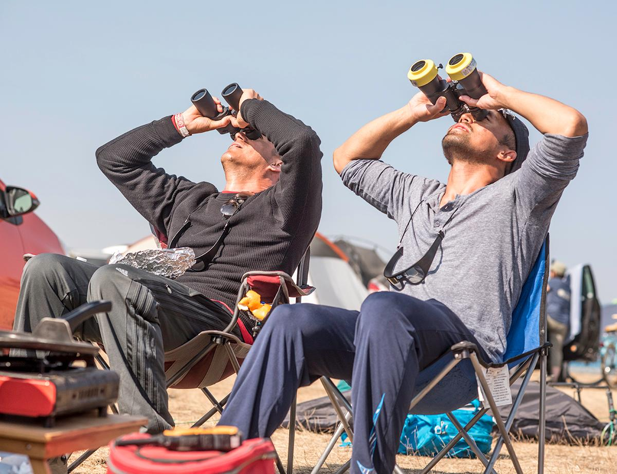 David Orellana and Phi Le look up at the eclipse through their solar filter binoculars. Photo by Cheyenne Thorpe, Oregon News Lab