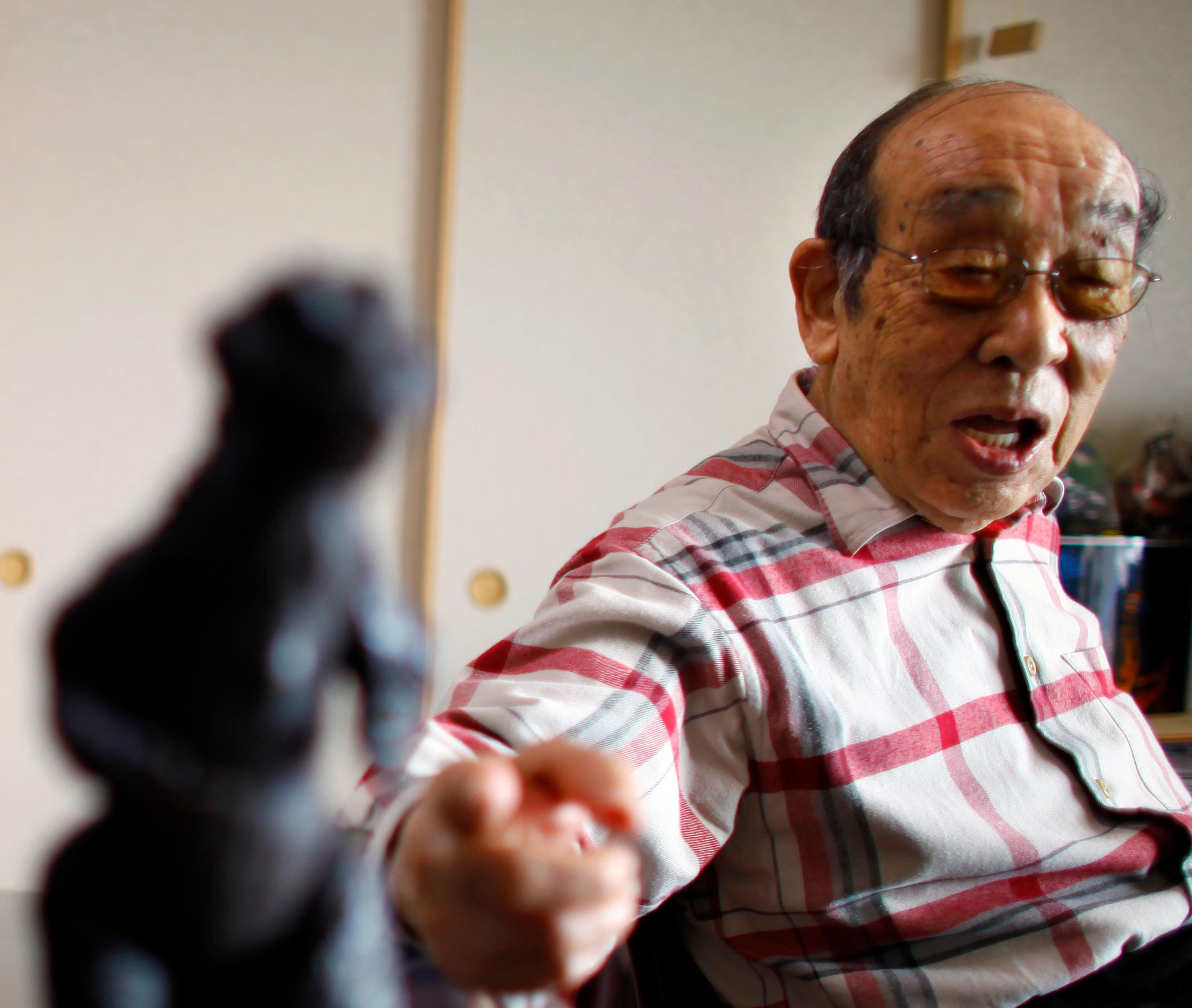 FILE - In this April 28, 2014 file photo, original Godzilla suit actor Haruo Nakajima, who has played his role as the monster, points a figure of the monster he made for the movie, as he speaks during an interview at his home in Sagamihara, near Tokyo. Nakajima, the actor who stomped in a rubber suit to portray the original 1954 Godzilla, has died on Monday, Aug. 7, 2017. He was 88. (AP Photo/Junji Kurokawa, File)