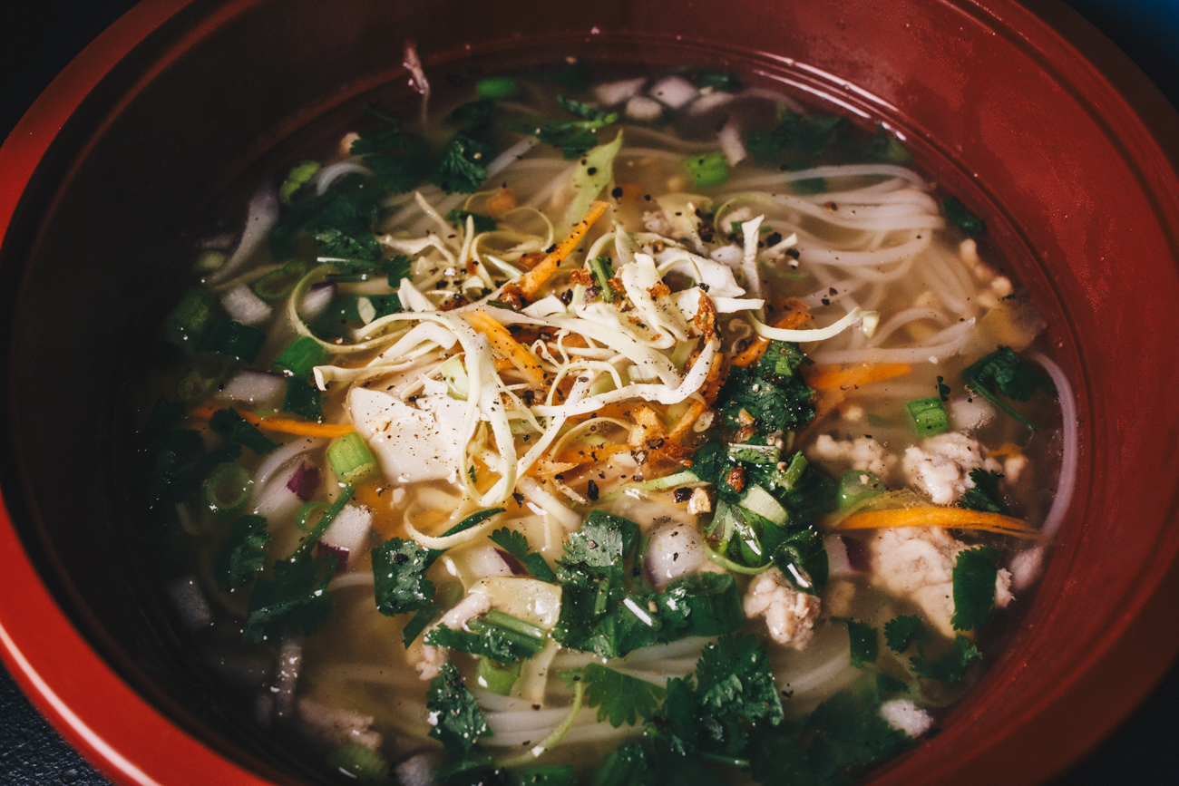 Bone broth kethlew : Cambodian pho soup garnished with cabbage, cilantro, and lime with rice noodles / Image: Catherine Viox // Published: 2.24.19