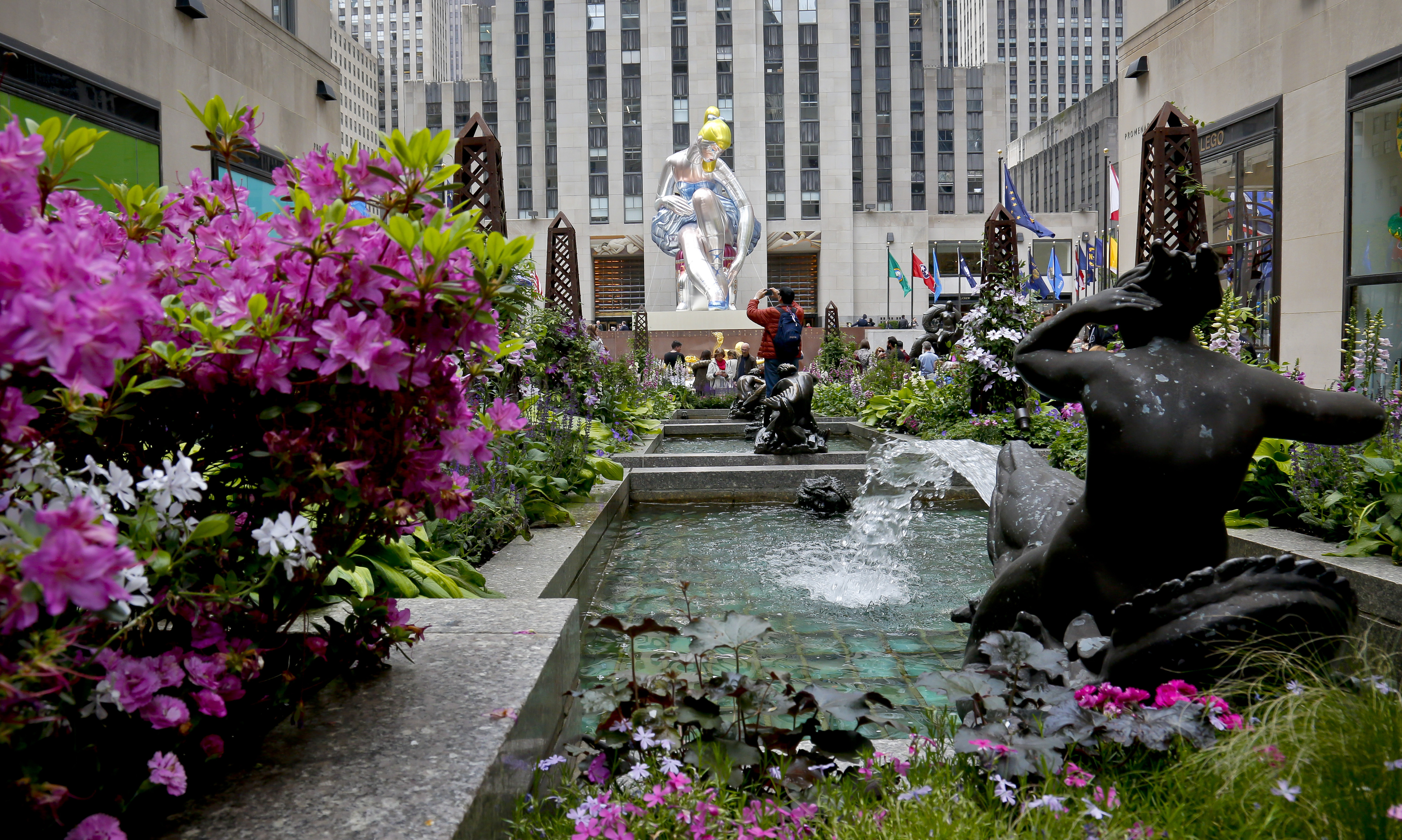 """Seated Ballerina"", at rear, the public art exhibition of a 45-foot tall inflatable nylon sculpture depicting a seated ballerina from artist Jeff Koons' Antiquity series, is displayed at Rockefeller Center after it was unveiled Friday May 12, 2017, in New York. (AP Photo/Bebeto Matthews)."