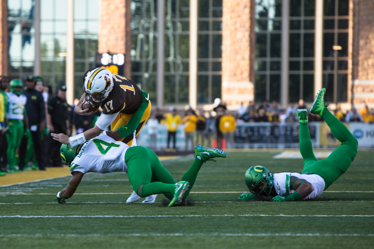 Wyoming quarterback Josh Allen (#17) dives over Oregon cornerback Thomas Graham Jr. (#4). The Oregon Ducks lead the Wyoming Cowboys 42 to 10 at the end of the first half on Saturday, September 16, 2017 in Laramie, Wyo. Photo by Austin Hicks, Oregon News Lab