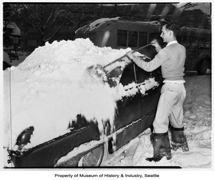 Record low temperatures and heavy snow plagued the Seattle area during the winter of 1950. On Friday January 13, downtown Seattle received an average of ten inches of snow, with Sea-Tac airport reporting 20 inches.  Although the snow let up on Saturday, the cold temperatures persisted for several more days. Seattle recorded nine days of temperatures below ten degrees between January 12 and February 4, 1950. In this photo, a man clears snow off a car on a Seattle street. (Photo: Museum of History & Industry, Seattle. Image: 1986.5.14570.1)