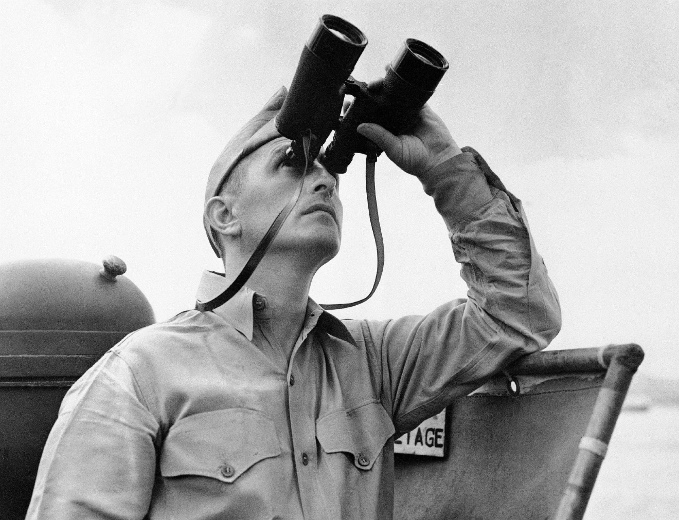 Eugene Burns, Associated Press war correspondent with the Pacific Fleet, stands on the deck of a Navy vessel with binoculars raised as he covered operations of a task force in the South Pacific in October 1942. (AP Photo)