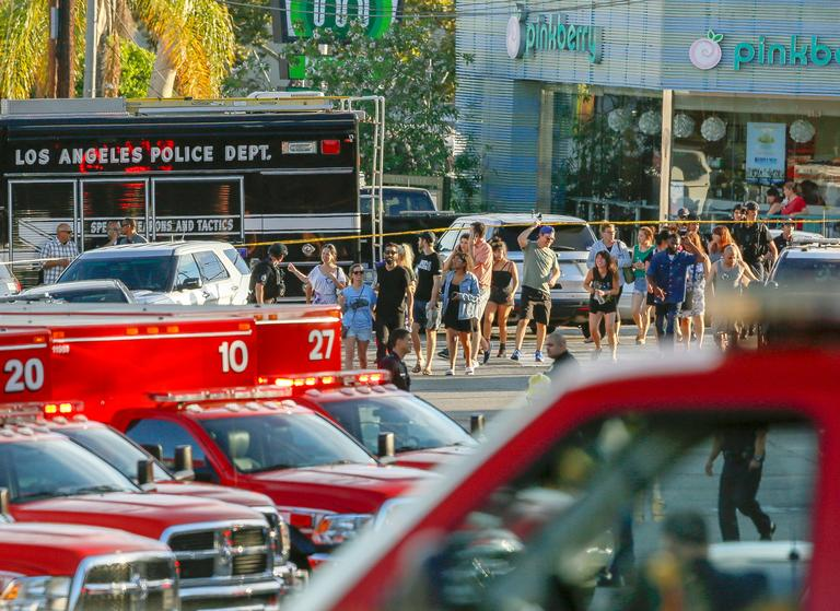 Los Angeles Police SWAT officers escort a group of people who were held for their safety by police across businesses surrounding a Trader Joe's supermarket, after a gunman held dozens of people hostage inside the store before surrendering to police in Los Angeles Saturday, July 21, 2018.  (AP Photo/Damian Dovarganes)
