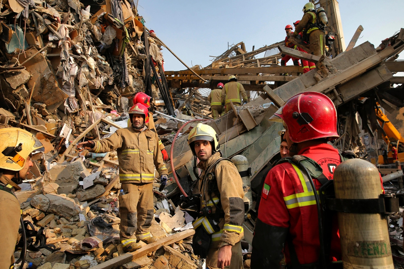 Iranian firefighters work at the scene of the collapsed Plasco building after being engulfed by a fire, in central Tehran, Iran, Thursday, Jan. 19, 2017. Iran's state-run Press TV says dozens of firefighters have been killed in the collapse of a burning high-rise building. (AP Photo/Ebrahim Noroozi)