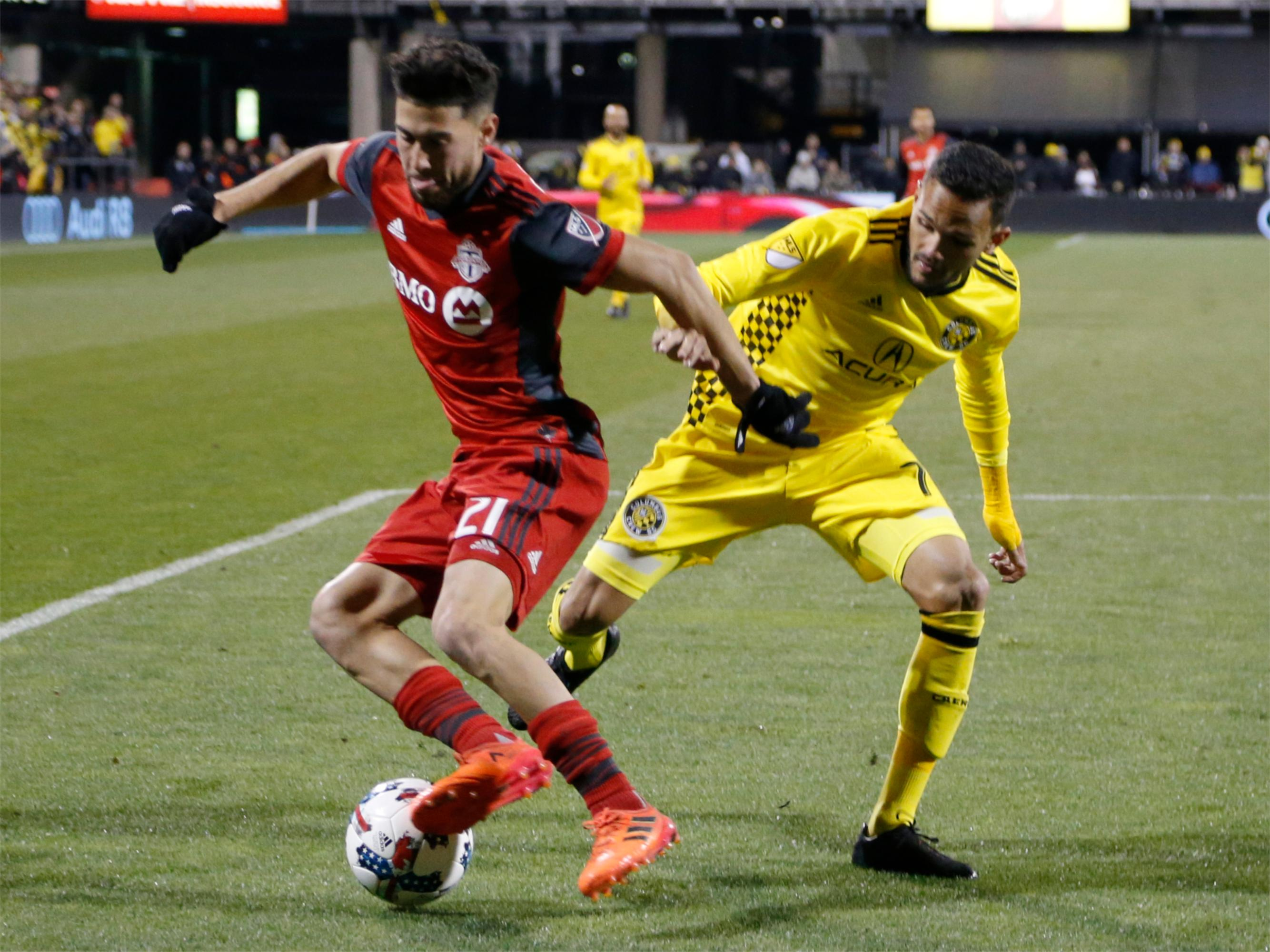 Toronto FC's Jonathan Osorio, left, and Columbus Crew's Artur fight for a loose ball during the second half of an MLS Eastern Conference championship soccer match Tuesday, Nov. 21, 2017, in Columbus, Ohio. The match ended in a 0-0 tie. (AP Photo/Jay LaPrete)