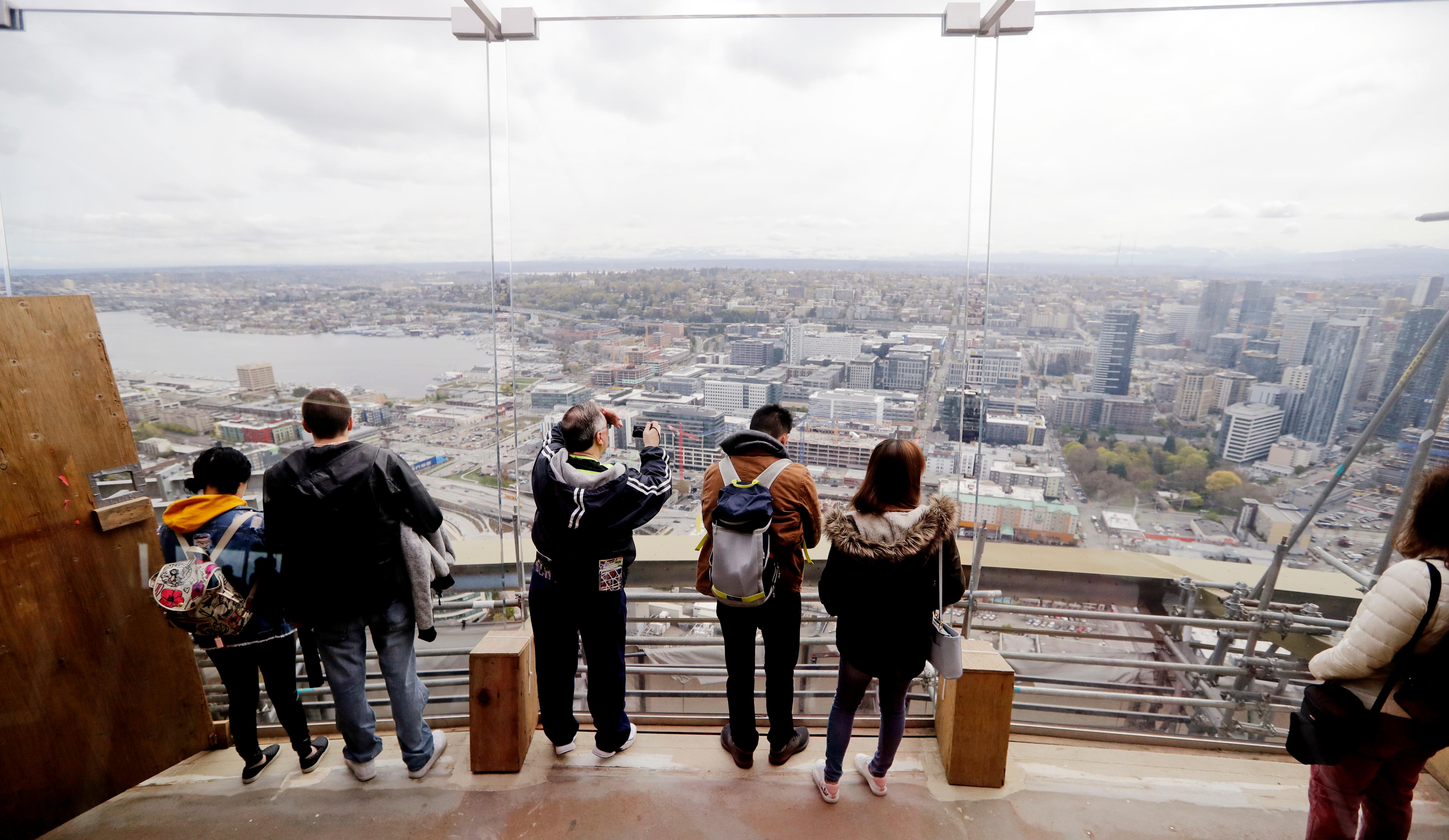 In this photo taken April 18, 2018, visitors to the viewing platform of the Space Needle look east through newly-installed glass panels in Seattle.{ } (AP Photo/Elaine Thompson)