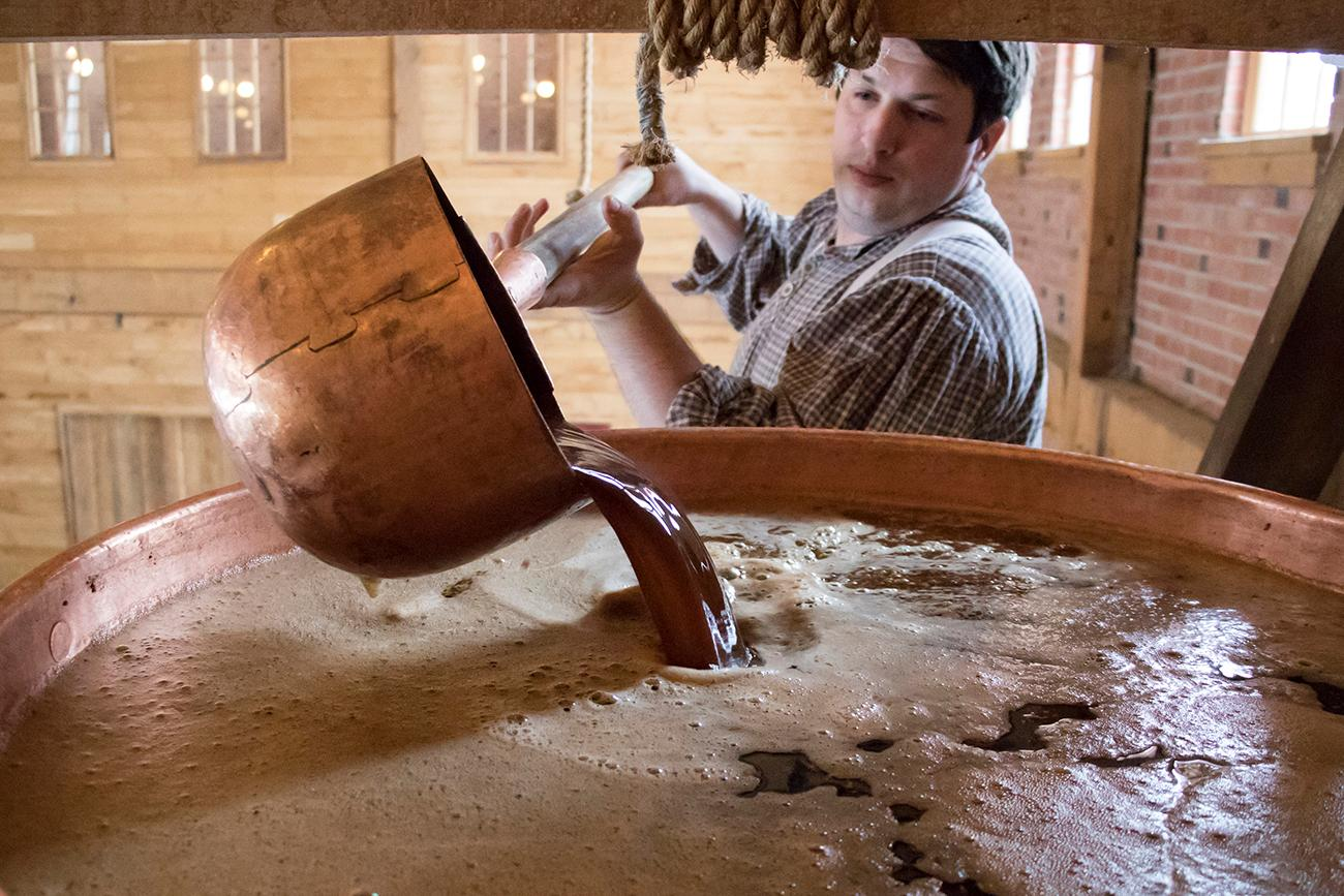 Milled malt steeps in the hot water to draw its sugars out into the water. The sugary water is called wort. Head Brewer, Kyle Spears, is shown hand ladling the wort. / Image: Allison McAdams // Published: 1.16.18