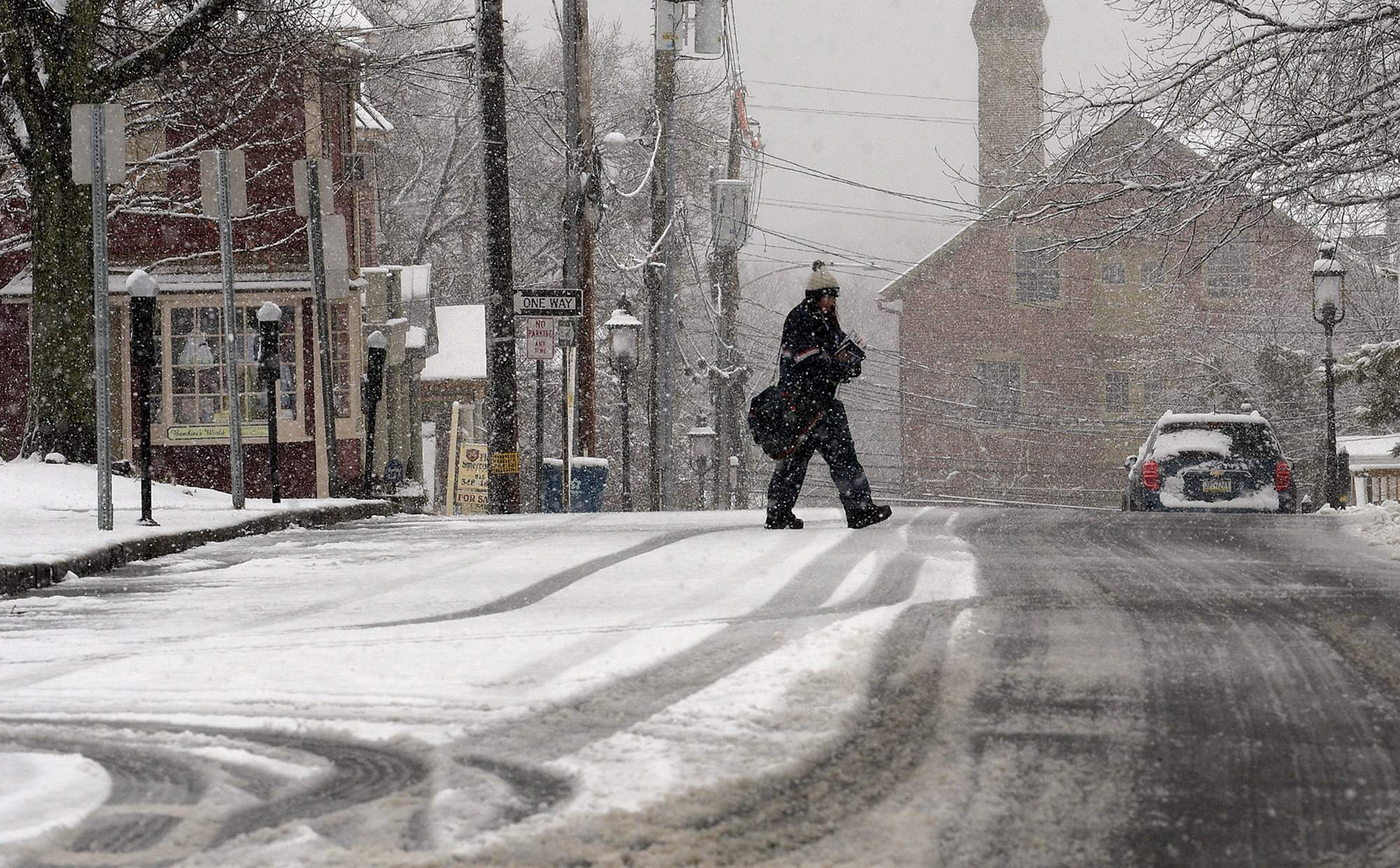 A postal worker delivers mail in the nearly deserted streets of Doylestown Borough on Wednesday, March 7, 2018, as businesses were shut down because of the storm. [KIM WEIMER / STAFF PHOTOJOURNALIST]