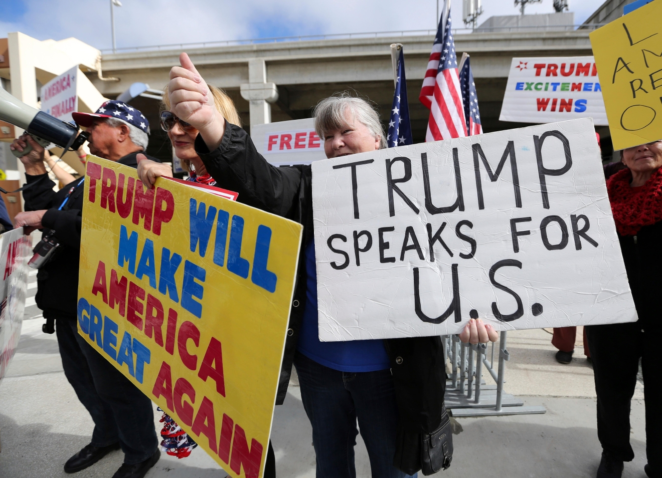 FILE - In this Feb. 4, 2017, file photo, a woman gives a thumbs up in Los Angeles, Calif., as demonstrators in favor of President Donald Trump's executive order banning travel to the U.S. from seven primarily Muslim nations stand across the street from the Tom Bradley International Terminal at Los Angeles International Airport. President Donald Trump's administration said in court documents on Thursday, Feb. 16, 2017, it wants an end to the legal fight over its ban on travelers from seven predominantly Muslim nations and will instead issue a replacement ban.  (AP Photo/Reed Saxon, File)
