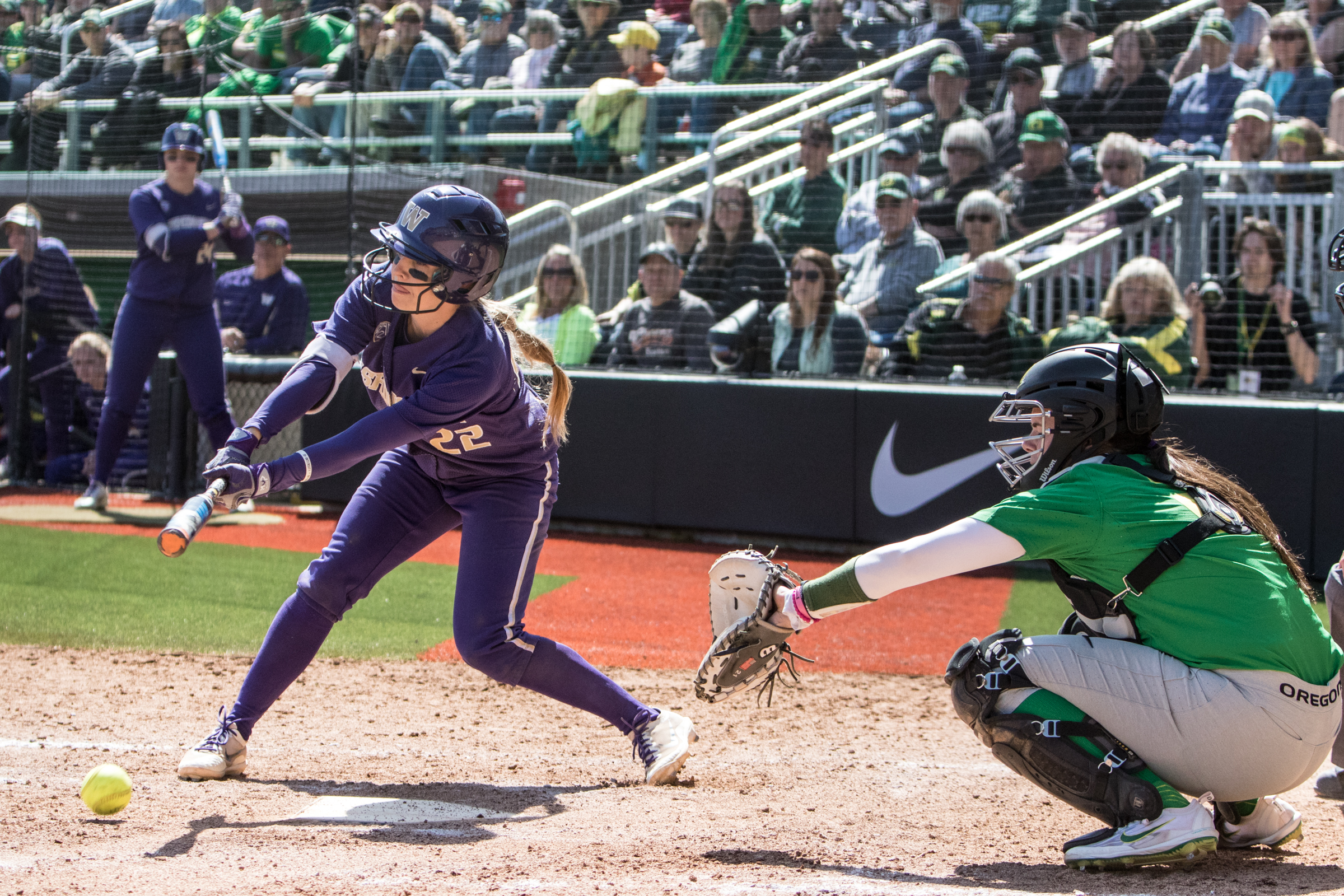 Washington Huskies infielder Sis Bates (#22) hits the ball down and into the ground. In the final game of a three-game series, the University of Washington Huskies defeated the Oregon Ducks 5-3.  The Ducks led through the bottom of the 7th inning, but Washington's Morganne Flores (#47) tied it up with a two-run double.  Flores drove in two more runs in the 9th to take the lead.  Photo by Austin Hicks, Oregon News Lab