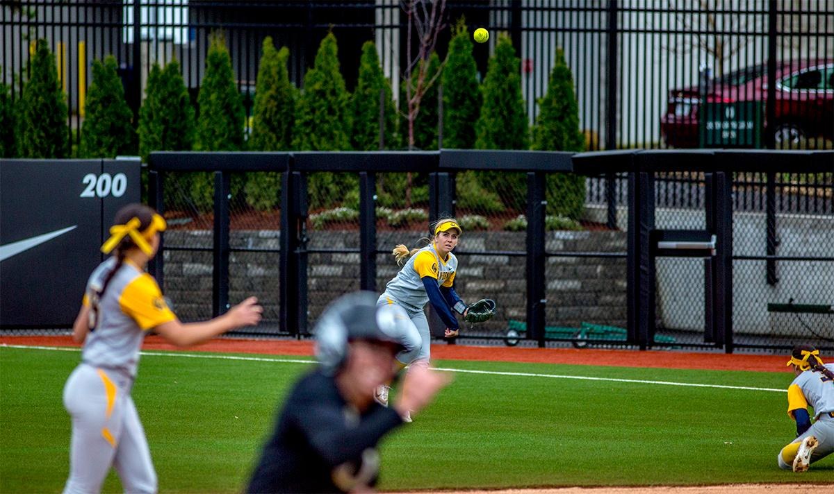 The Golden Bears' Bradie Fillmore (#4) throws the ball as a Ducks player runs for the base. The Oregon Ducks defeated the Cal Golden Bears 2-1 in the second game of the three game series. Photo by August Frank, Oregon News Lab