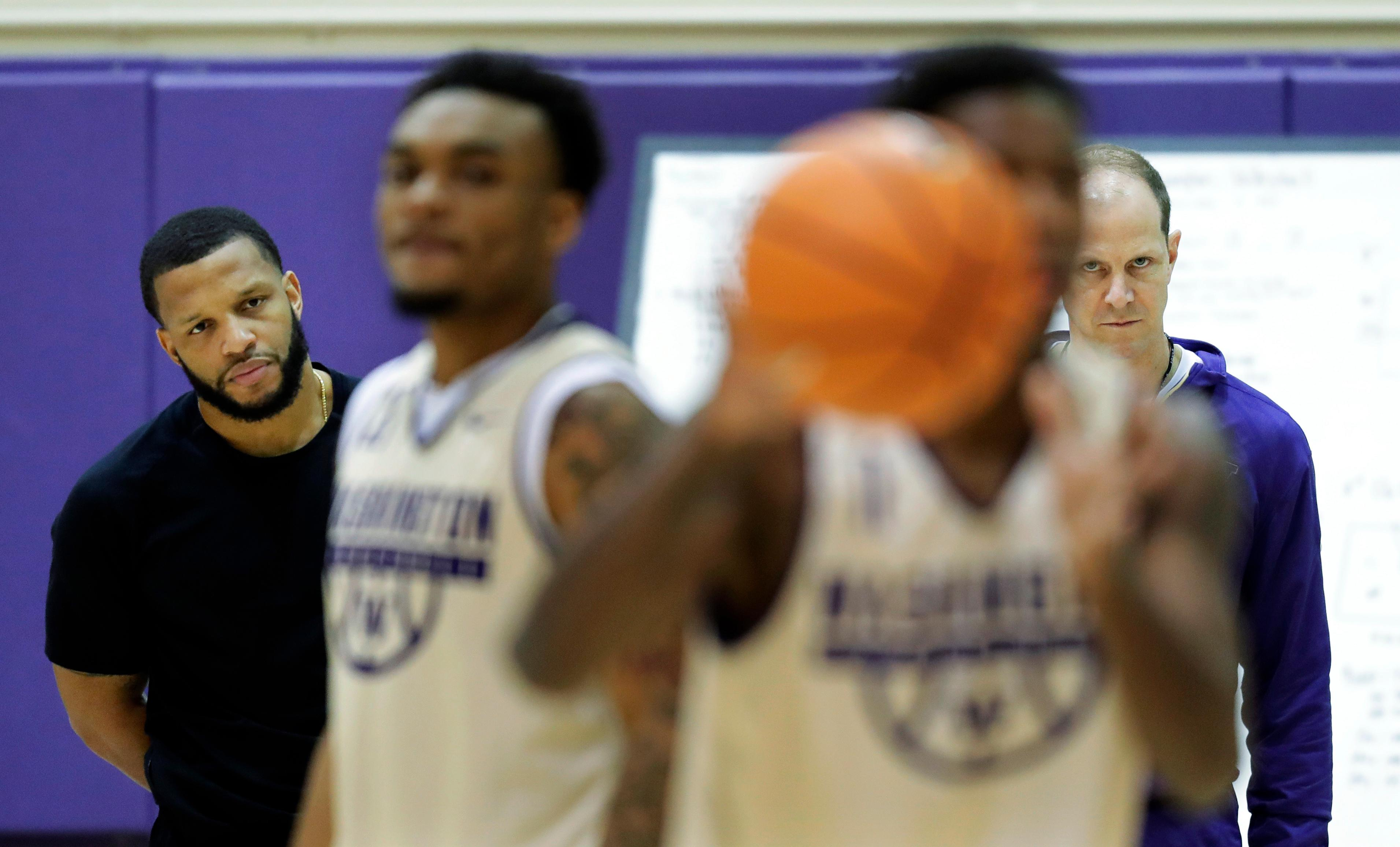 In this Friday, Jan. 26, 2018 photo Washington head coach Mike Hopkins, right, and assistant coach Will Conroy, left, watch as guards Carlos Johnson, second from left, and David Crisp, second from right, take part in a drill during NCAA college basketball practice in Seattle. One of the most surprising stories in college basketball is what Hopkins is doing in his first season at Washington and how the Huskies are in the conversation for an NCAA bid entering February. (AP Photo/Ted S. Warren)