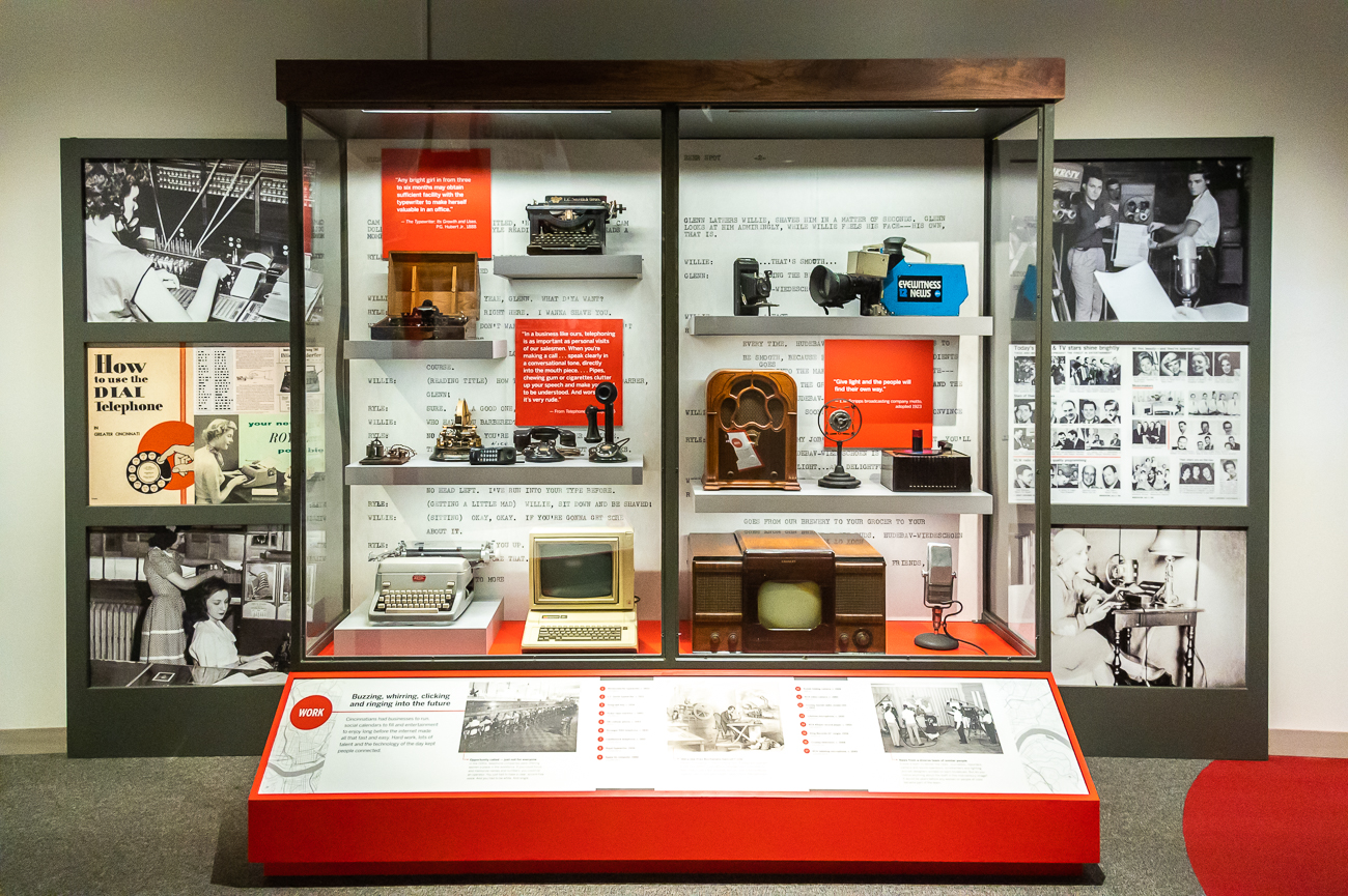 In addition to the ArtWorks interactive mural, upright glass displays showcase everything from photos to clothing that are related to living, working, and playing in Cincinnati throughout its history. This one showcases Cincinnati's history with communication and broadcast technology. / Image: Phil Armstrong, Cincinnati Refined // Published: 10.23.20