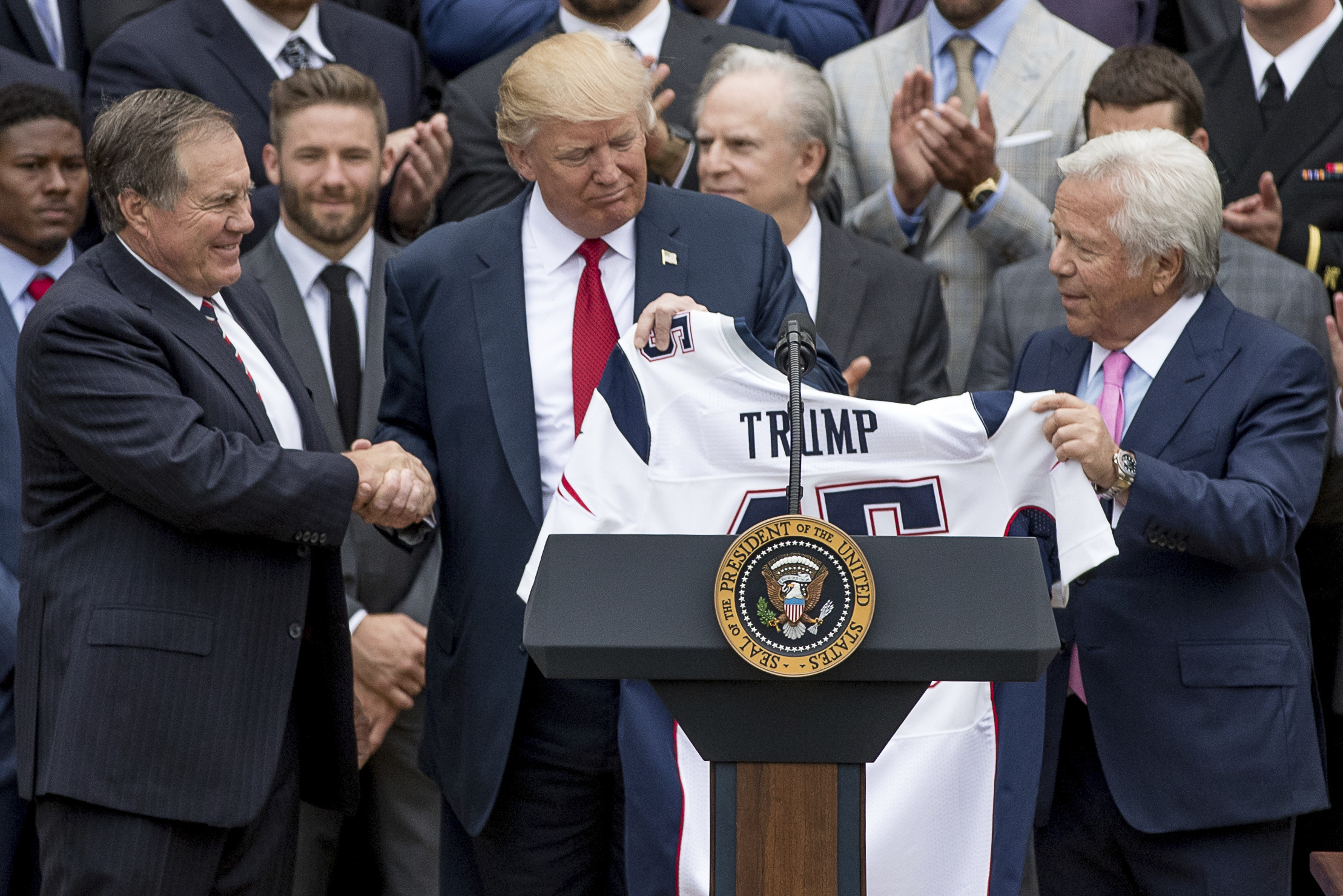 President Donald Trump is presented with a New England Patriots jersey by Patriots head coach Bill Belichick, left, and New England Patriots owner Robert Kraft during a ceremony on the South Lawn of the White House in Washington, Wednesday, April 19, 2017, where the president honored the Super Bowl Champion New England Patriots for their Super Bowl LI victory. (AP Photo/Andrew Harnik)